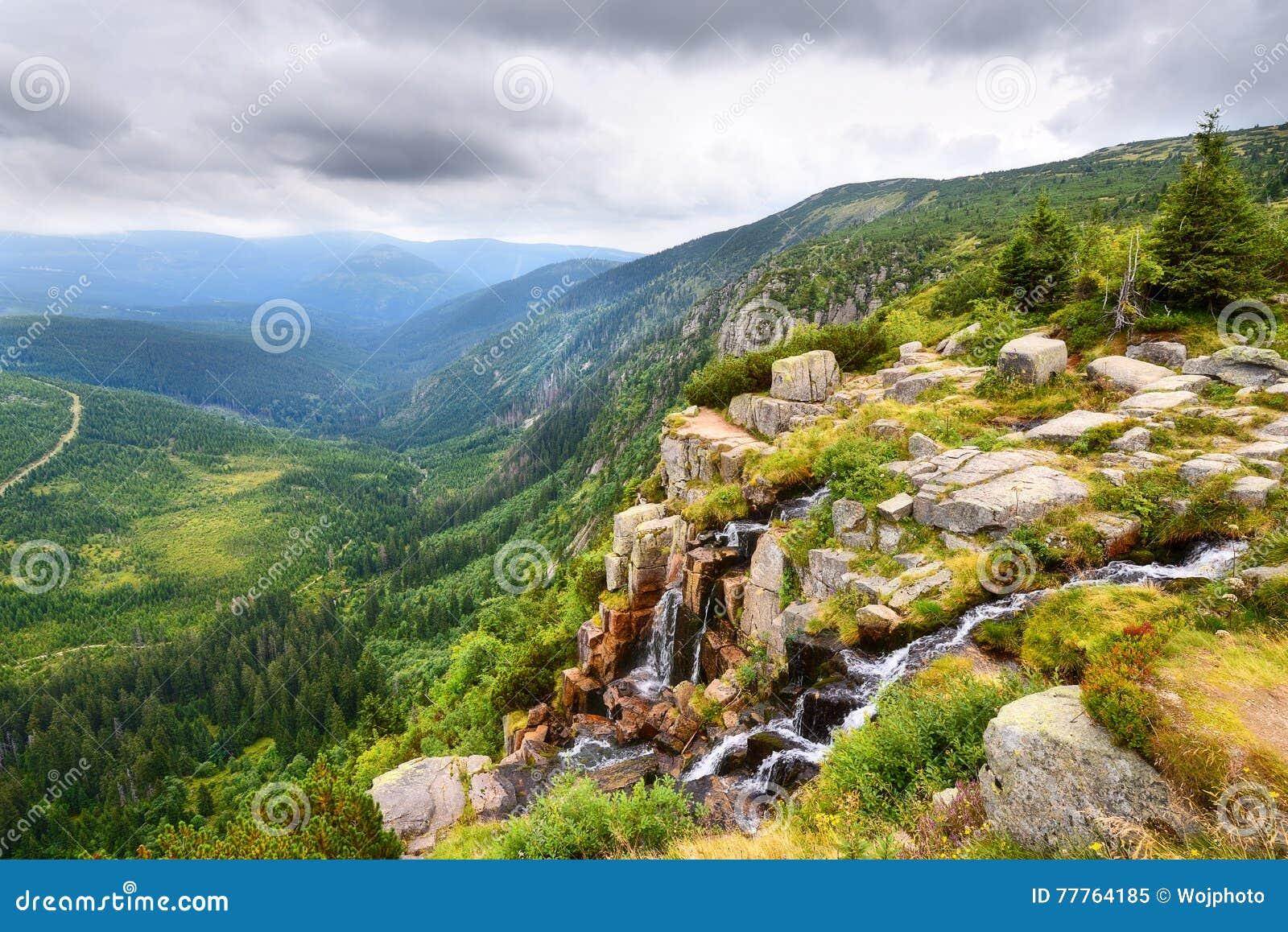 Mooie waterval boven een donkergroene vallei in de bergen