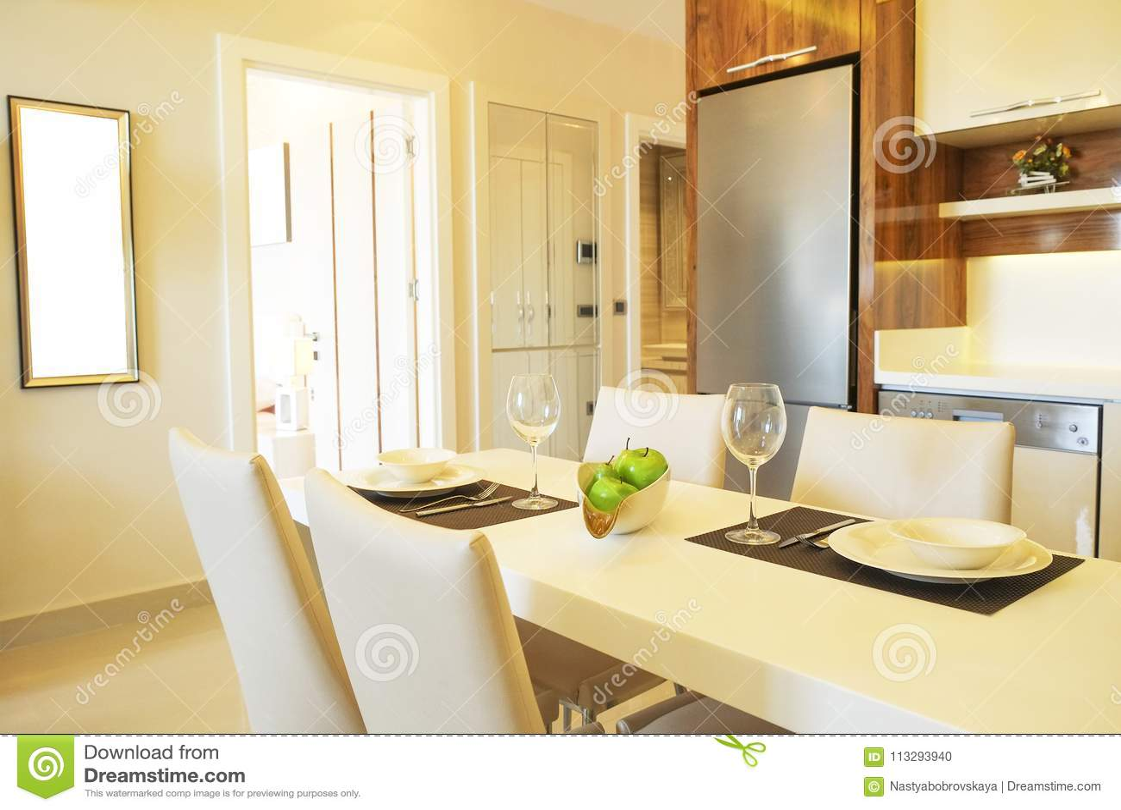 Mooie zon zijflat met eenvoudig minimalistic modern binnenlands ontwerp, de open woonkamer van de plankeuken in zonlicht