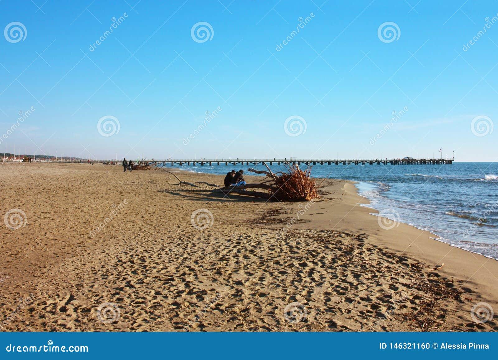 Mooie zonnige de winterdag op het zandige strand van Versilia in Forte dei Marmi De werf op de horizon, een weinig blauwe overzee