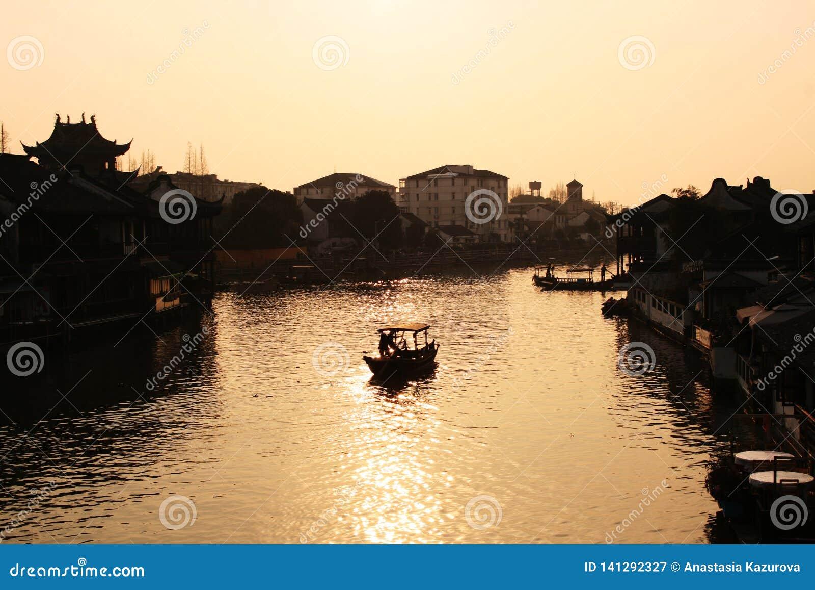 Mooie zonsondergang in de oude stad van Zhujiajiao, China Traditionele Chinese arhitecture, schepen op water, rivier