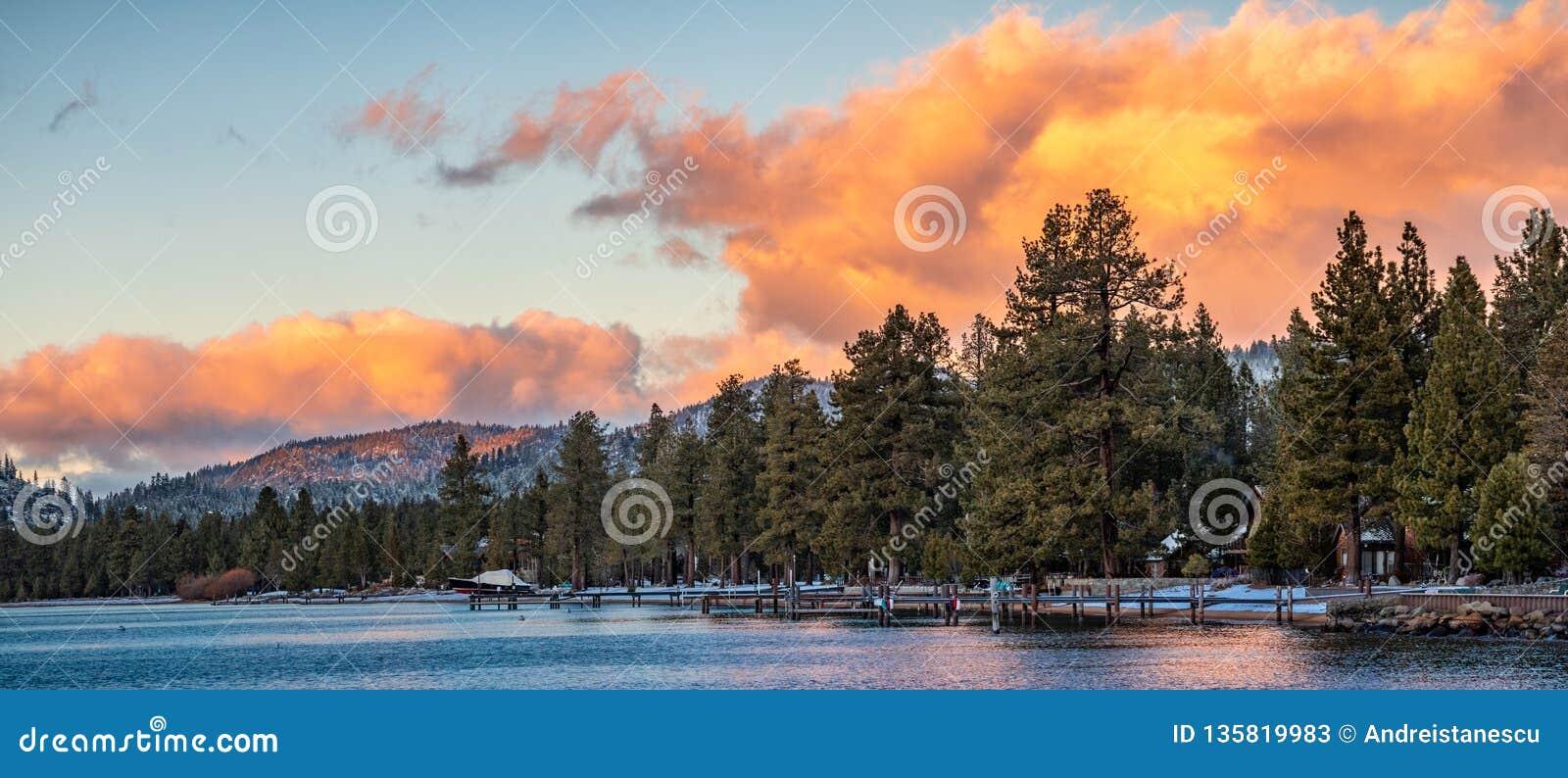 Mooie zonsondergangmeningen van de oever van Zuidenmeer Tahoe, huizen zichtbaar onder pijnboombomen