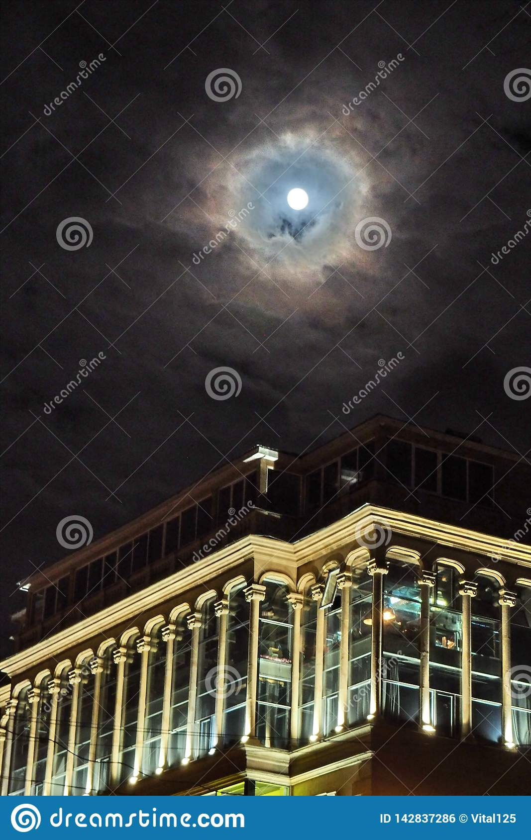 Moon and clouds observing over city