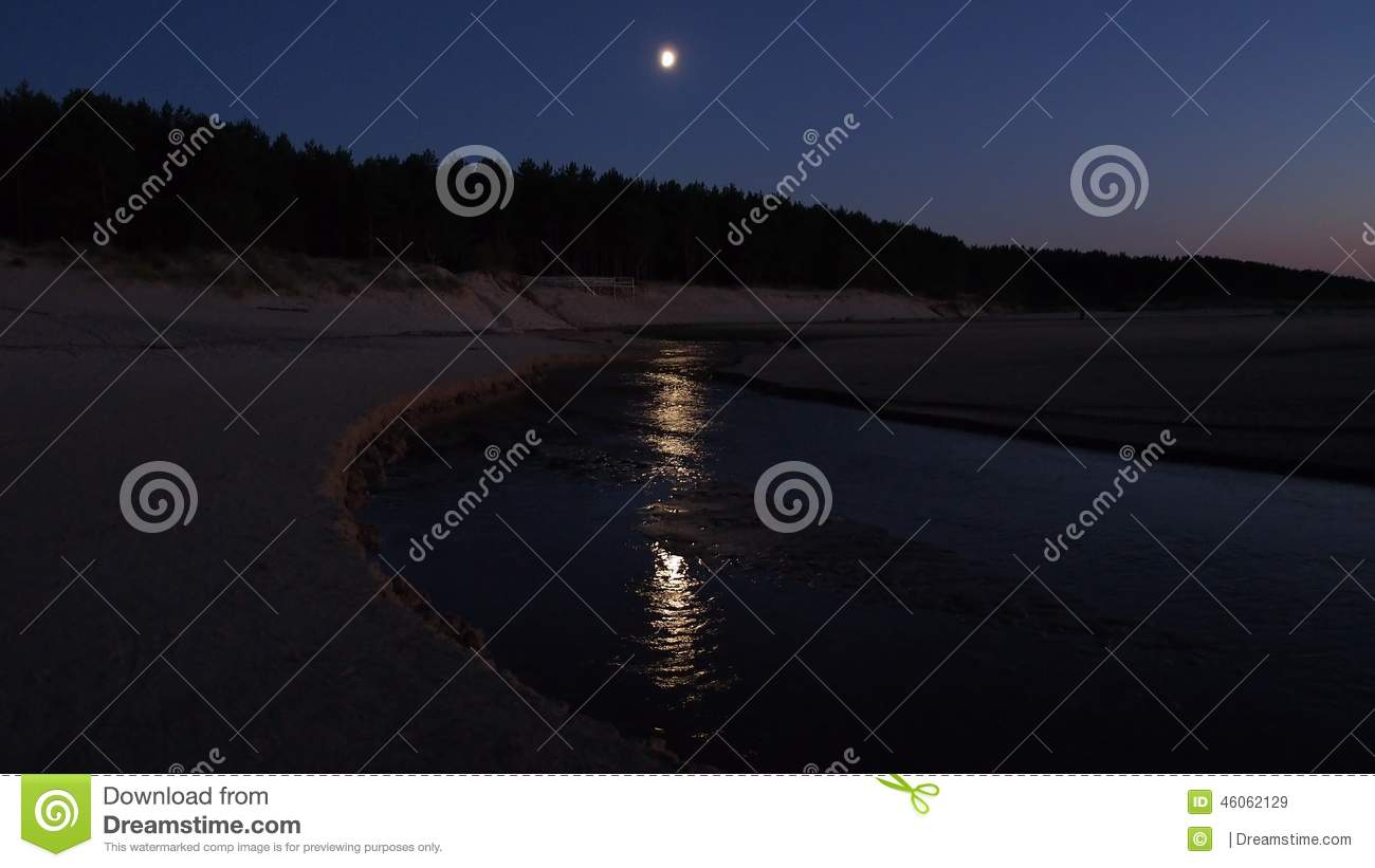 Moon in blue sky over sea and light reflection