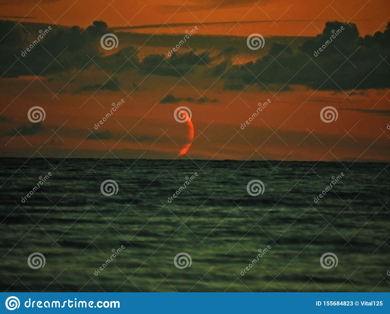 Red moon set over sea observing and clouds after sunset