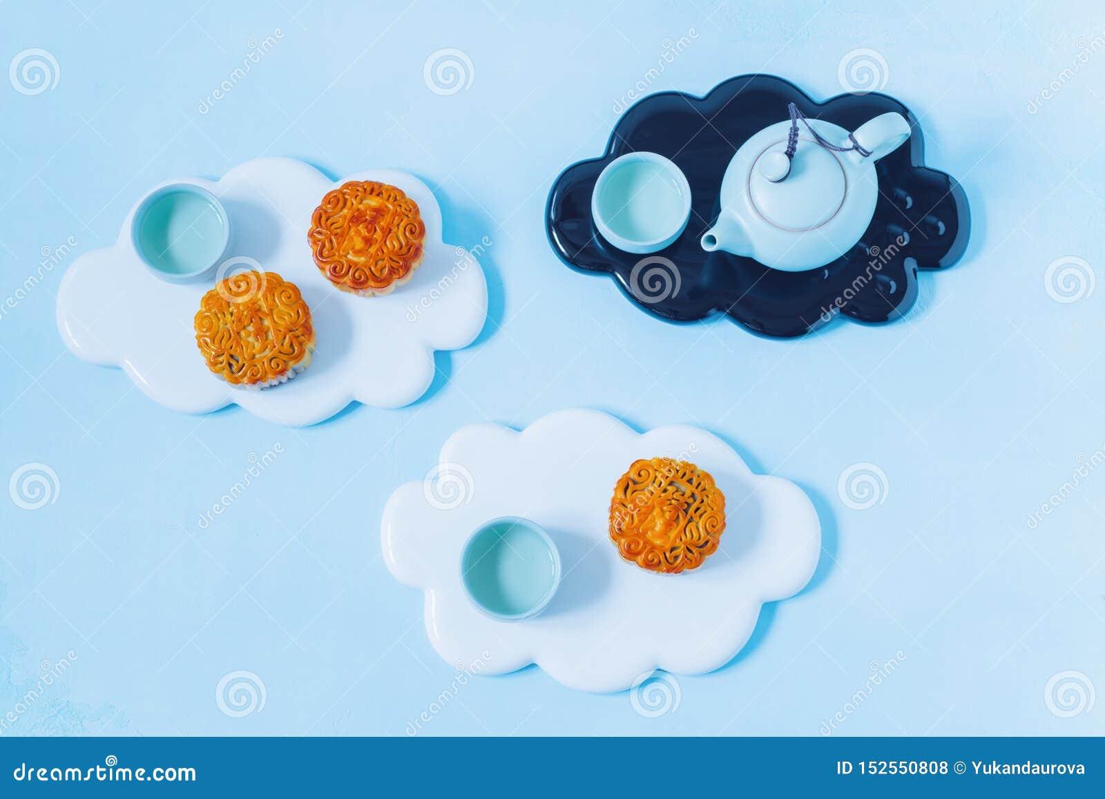 Mooncake, théière bleue, fleurs jaunes de chrysanthème sur le fond bleu Nourriture chinoise de festival de mi-automne