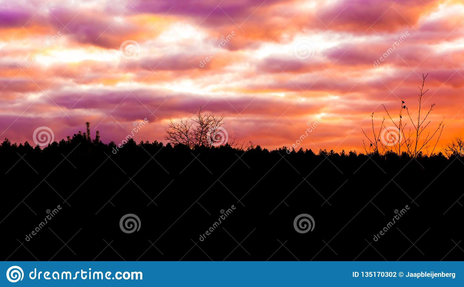 Moorland landscape at sunset with nacreous clouds, a rare winter weather effect