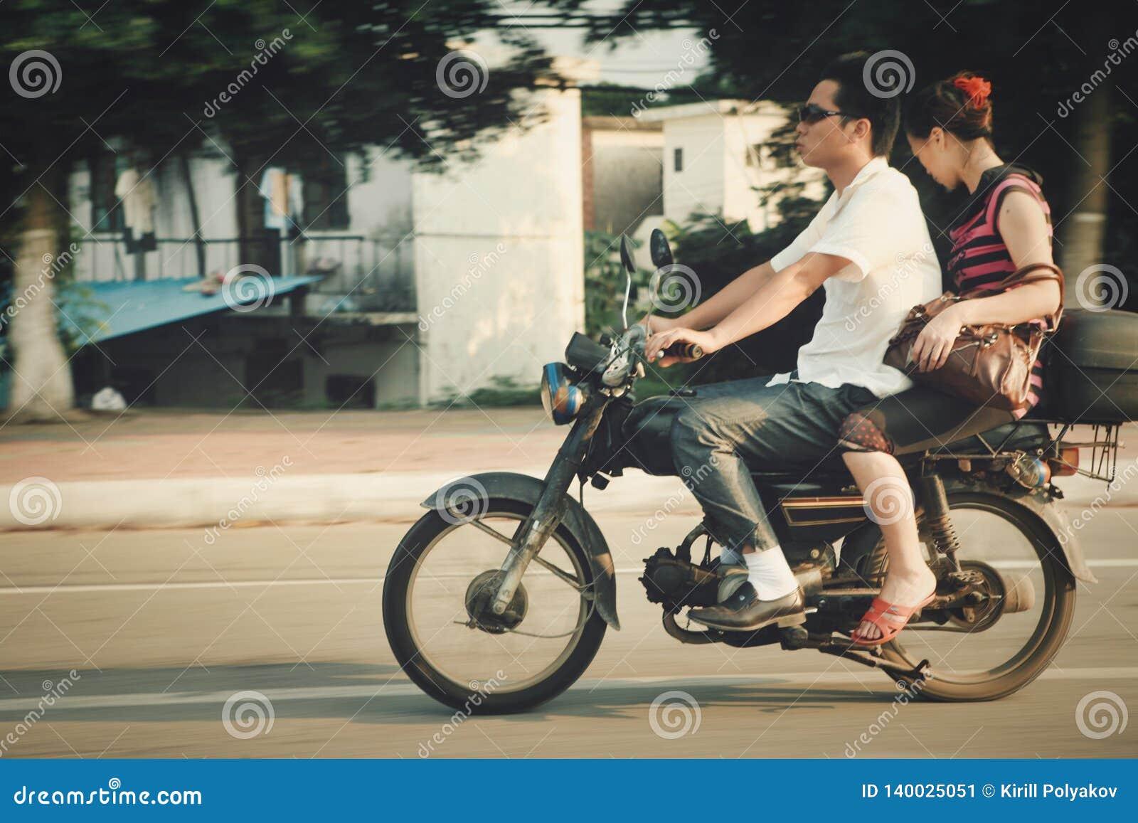 Guangzhou, China - July 22, 2018: Man and woman riding a motorcycle down the street in Guangzhou