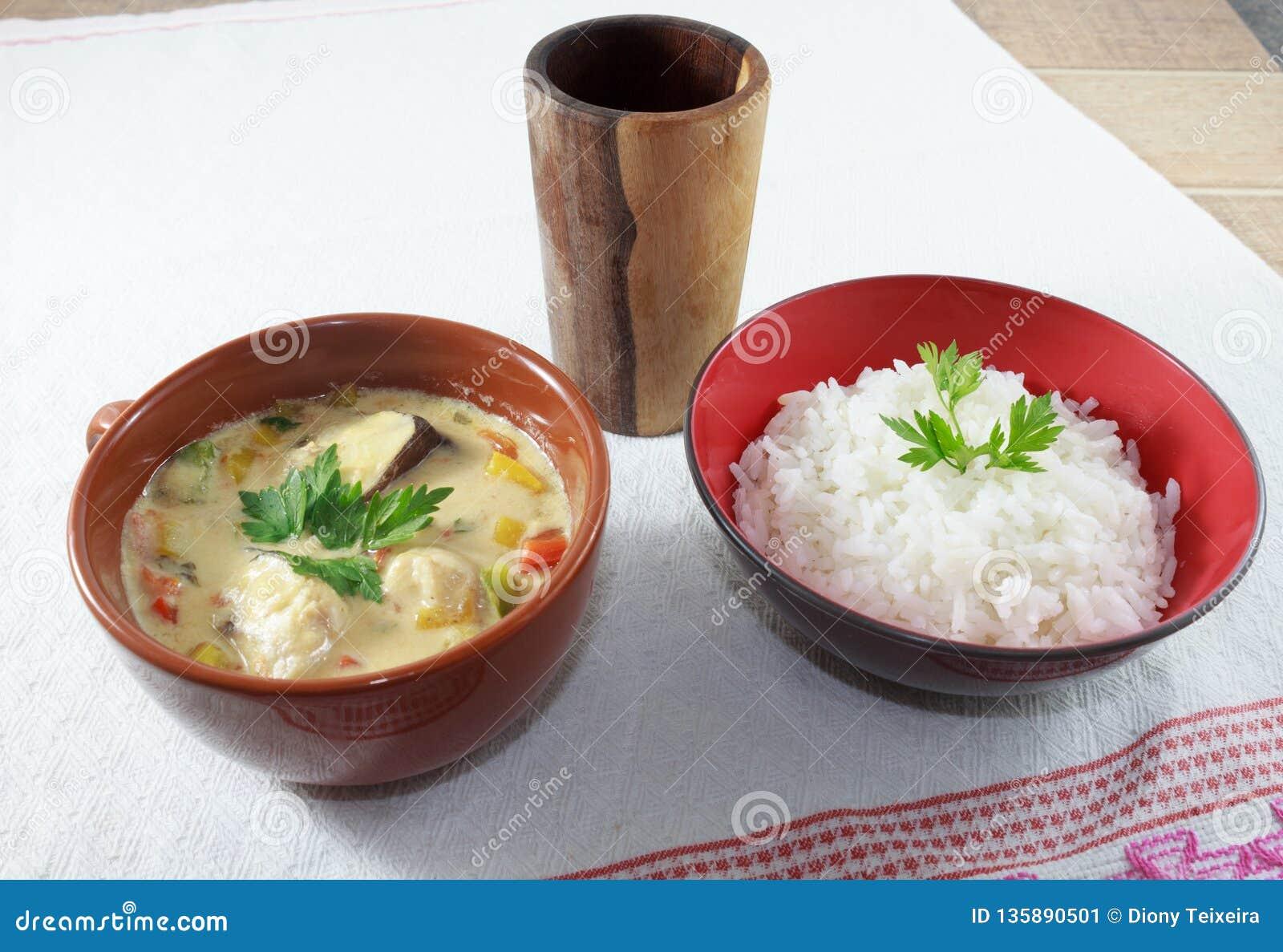 Moqueca av fisken och spanska peppar, matbrasilian som tjänas som med vita ris, på en trätabell