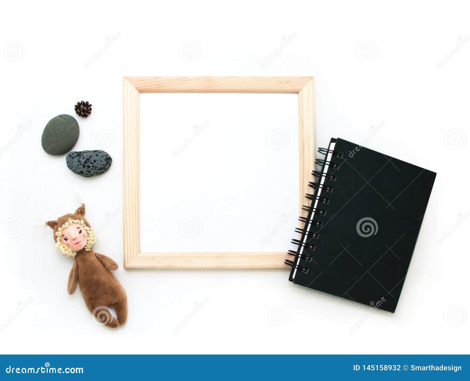 Moquerie étendue plate, vue supérieure, cadre en bois, écureuil de jouet, pierres, bloc-notes noir r