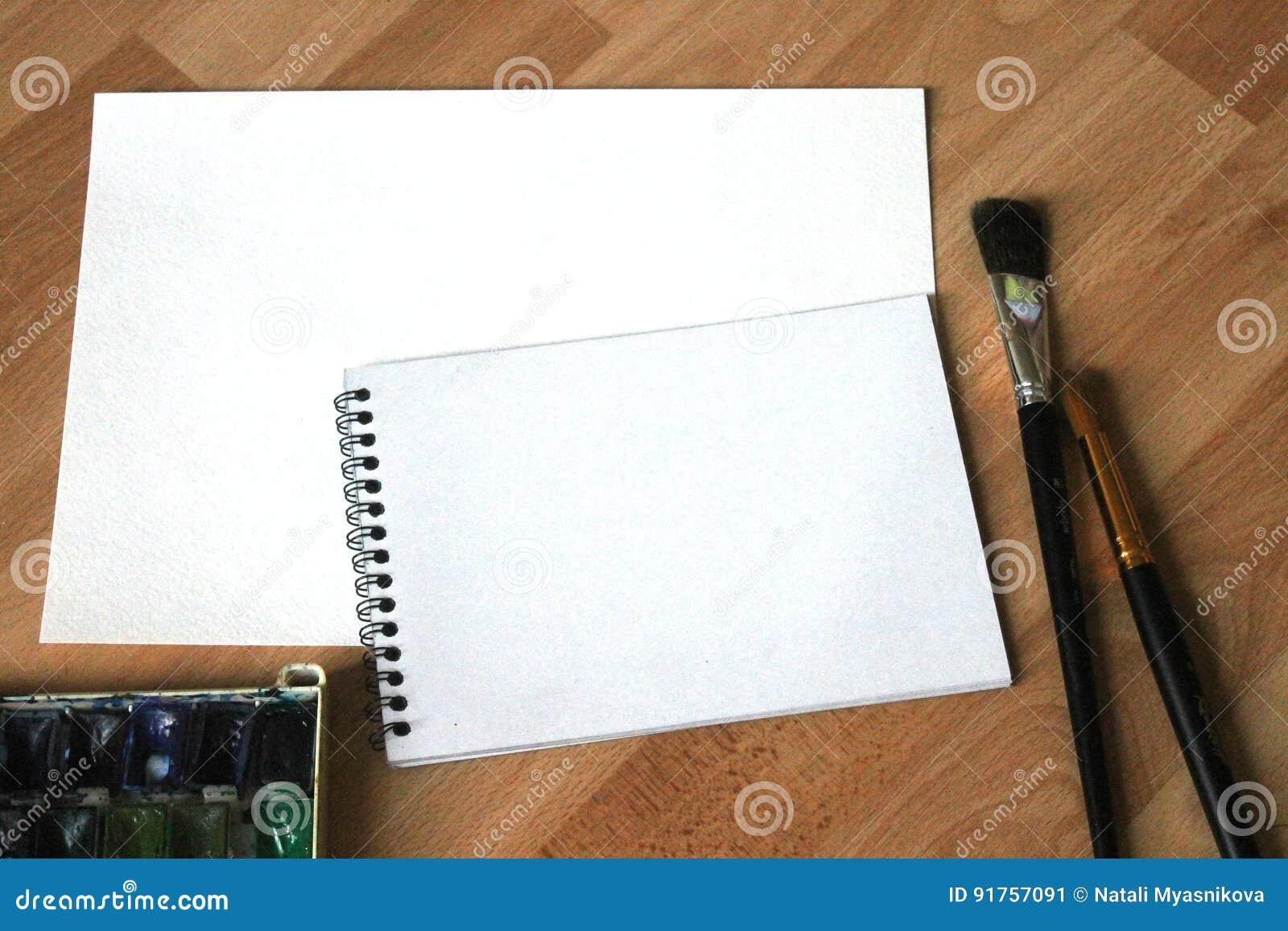 Moquerie de carnet pour l illustration avec des peintures d aquarelle, palette, verre de l eau et pinceaux Outils artistiques de