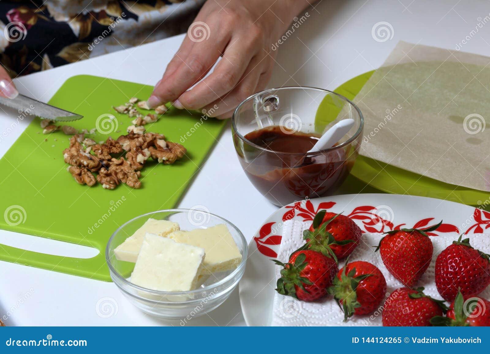 Morangos, chocolate preto e branco Porcas das costeletas da mulher Cozinhar morangos vitrificou no chocolate