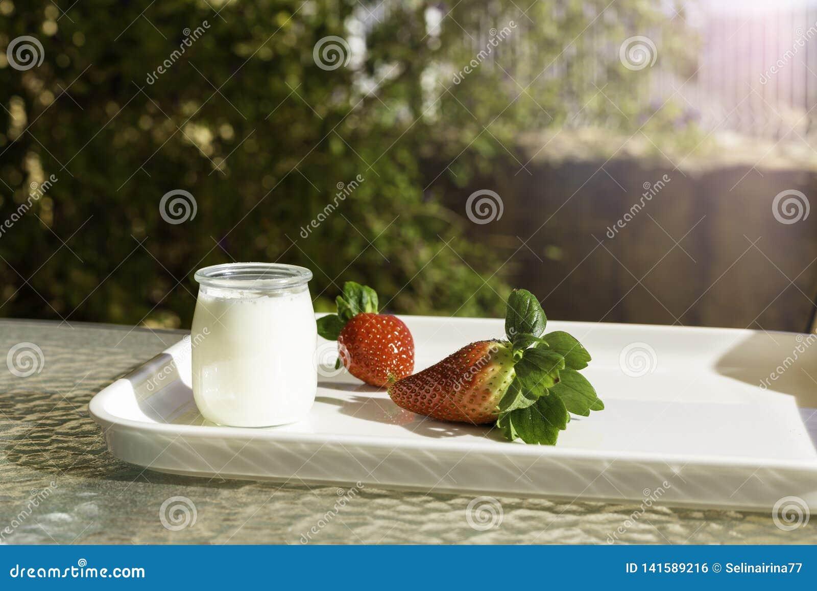 Morangos vermelhas frescas e iogurte branco em um frasco de vidro em uma bandeja branca em uma tabela no jardim ou no terraço em