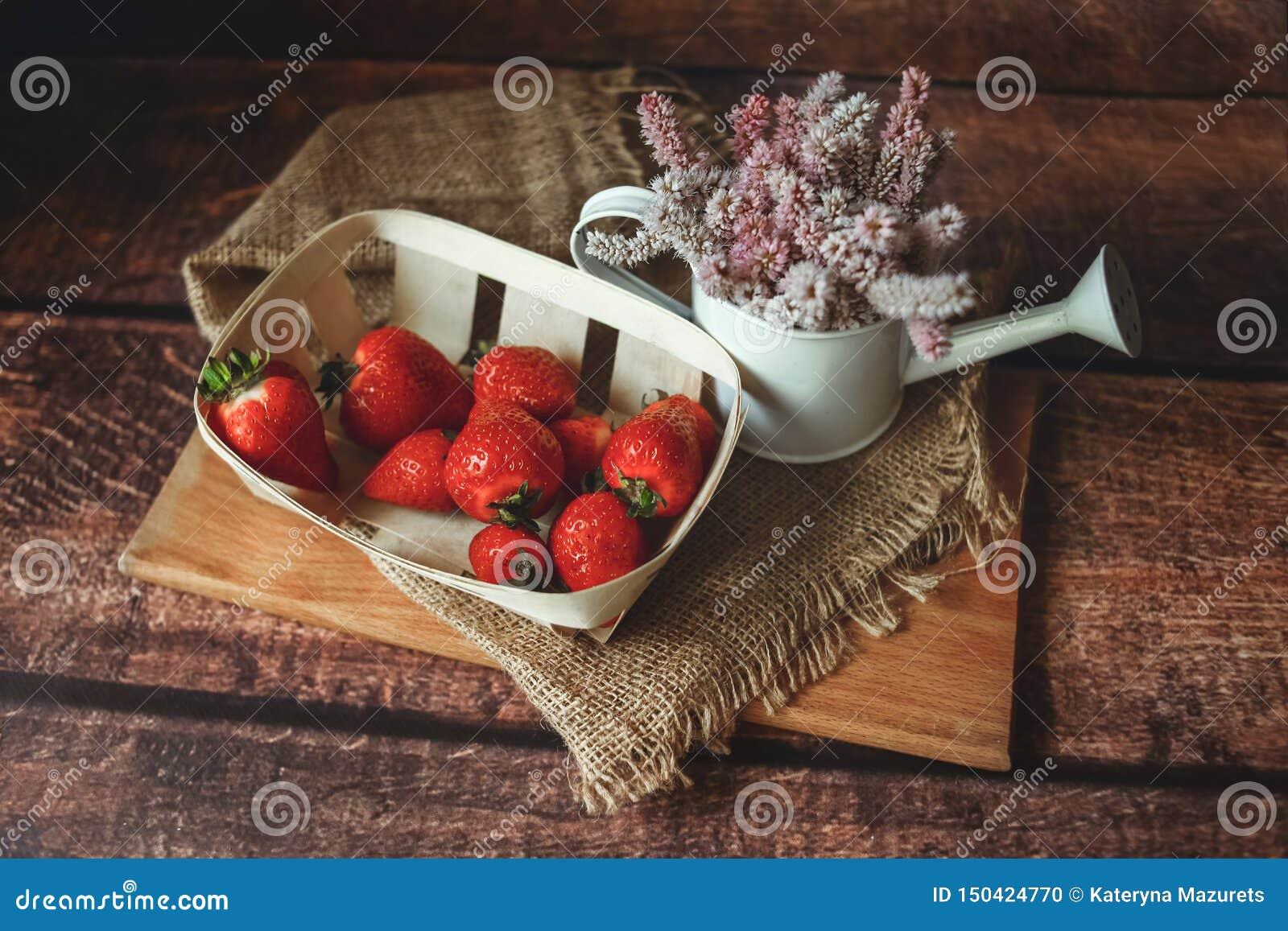 Morangos vermelhas frescas na tabela de madeira