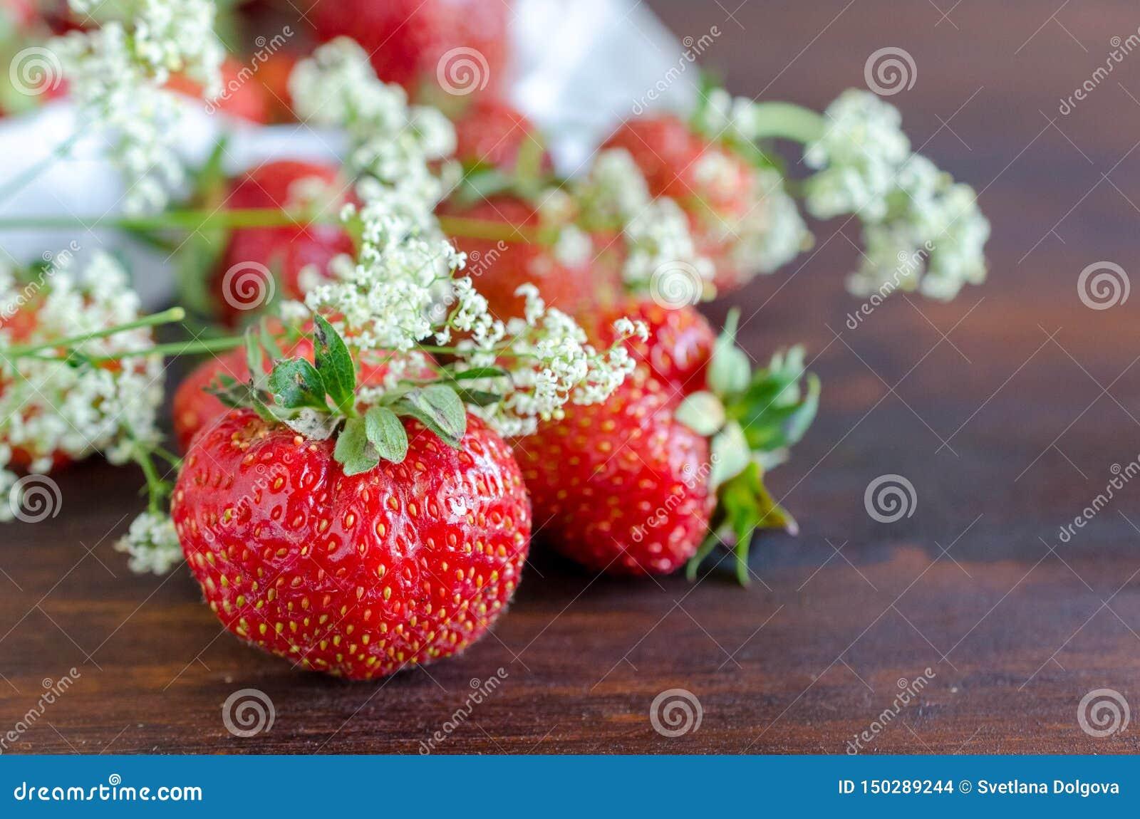 Morangos vermelhas maduras e flores selvagens brancas no verão