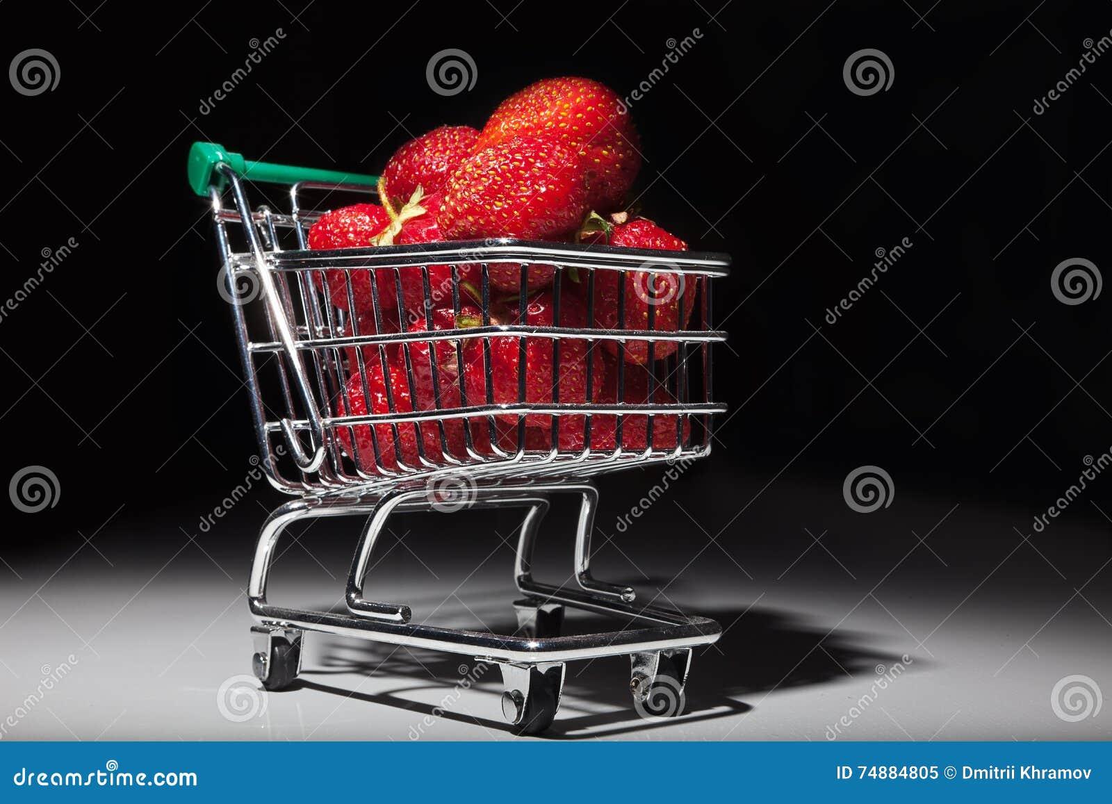 Morangos vermelhas maduras no trole diminuto do supermercado
