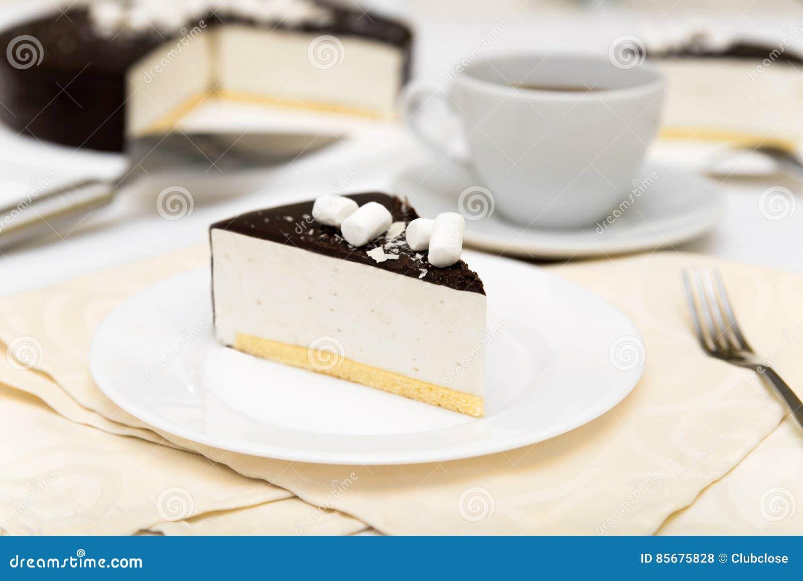 Morceau de gâteau avec le ` de lait du ` s d oiseau de ` de soufflé, le biscuit, la mousse et le chocolat de noir d un plat blanc