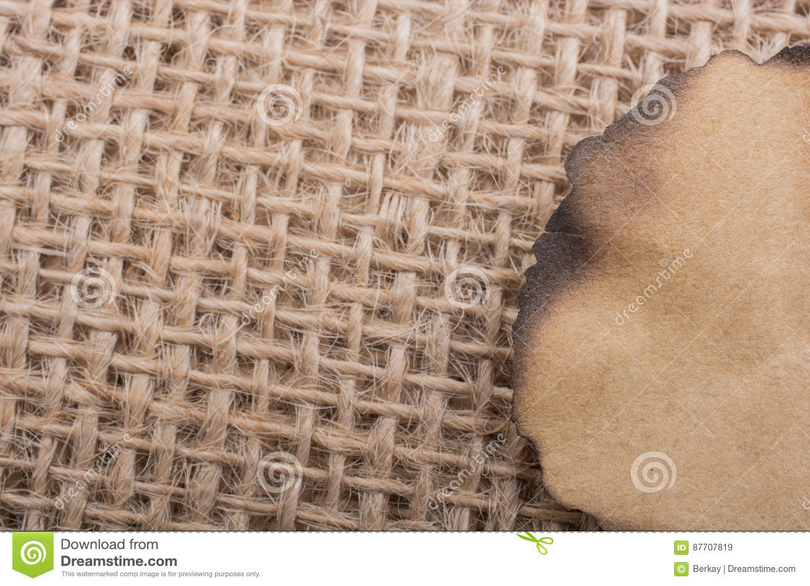 Morceau de papier brûlé sur une toile de toile