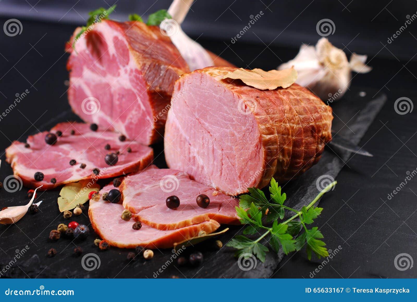 Morceaux de jambon fumé fait maison de porc sur le fond noir