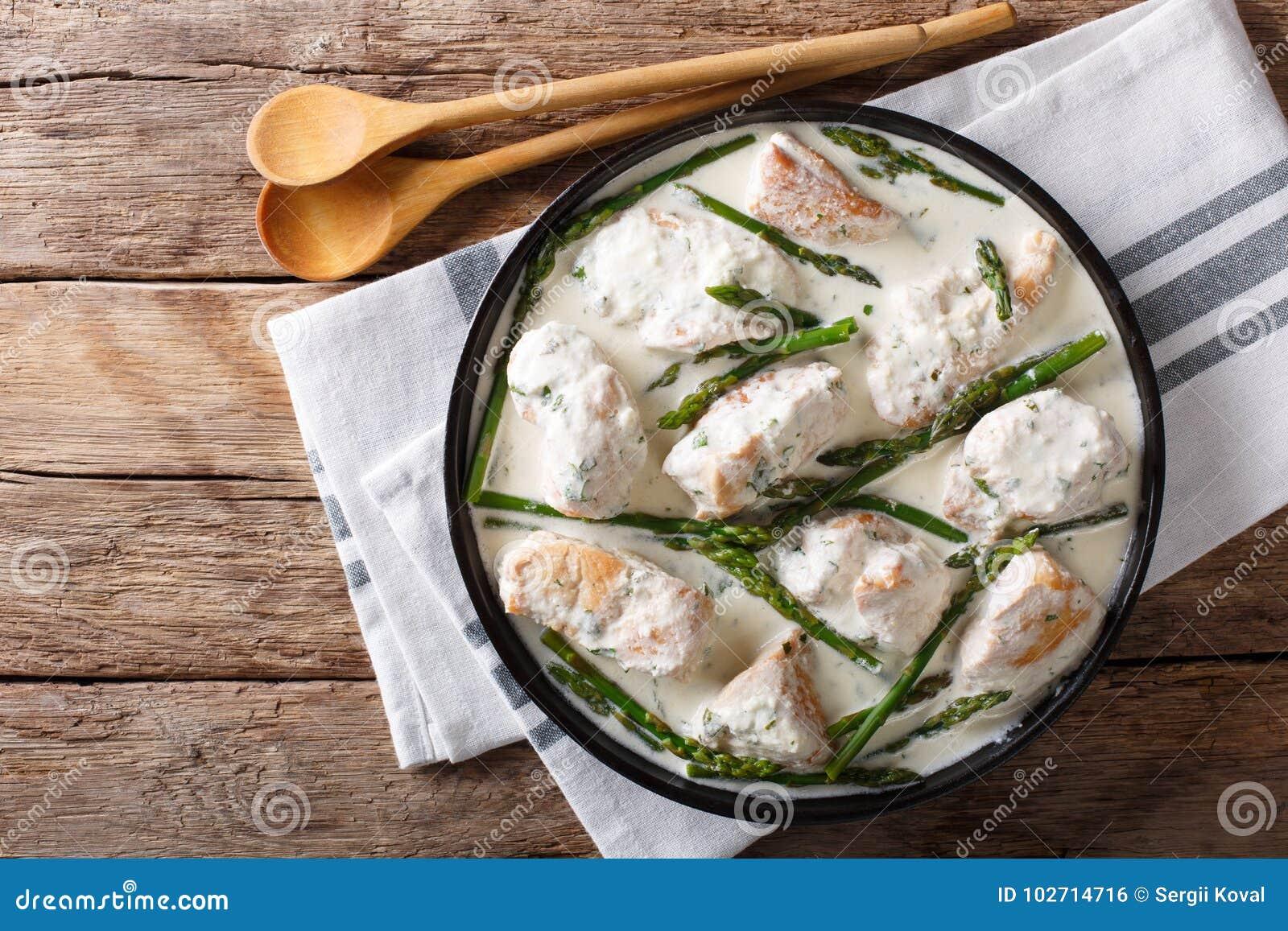 Morceaux de poulet avec l asperge de bébé dans un plan rapproché crémeux de sauce