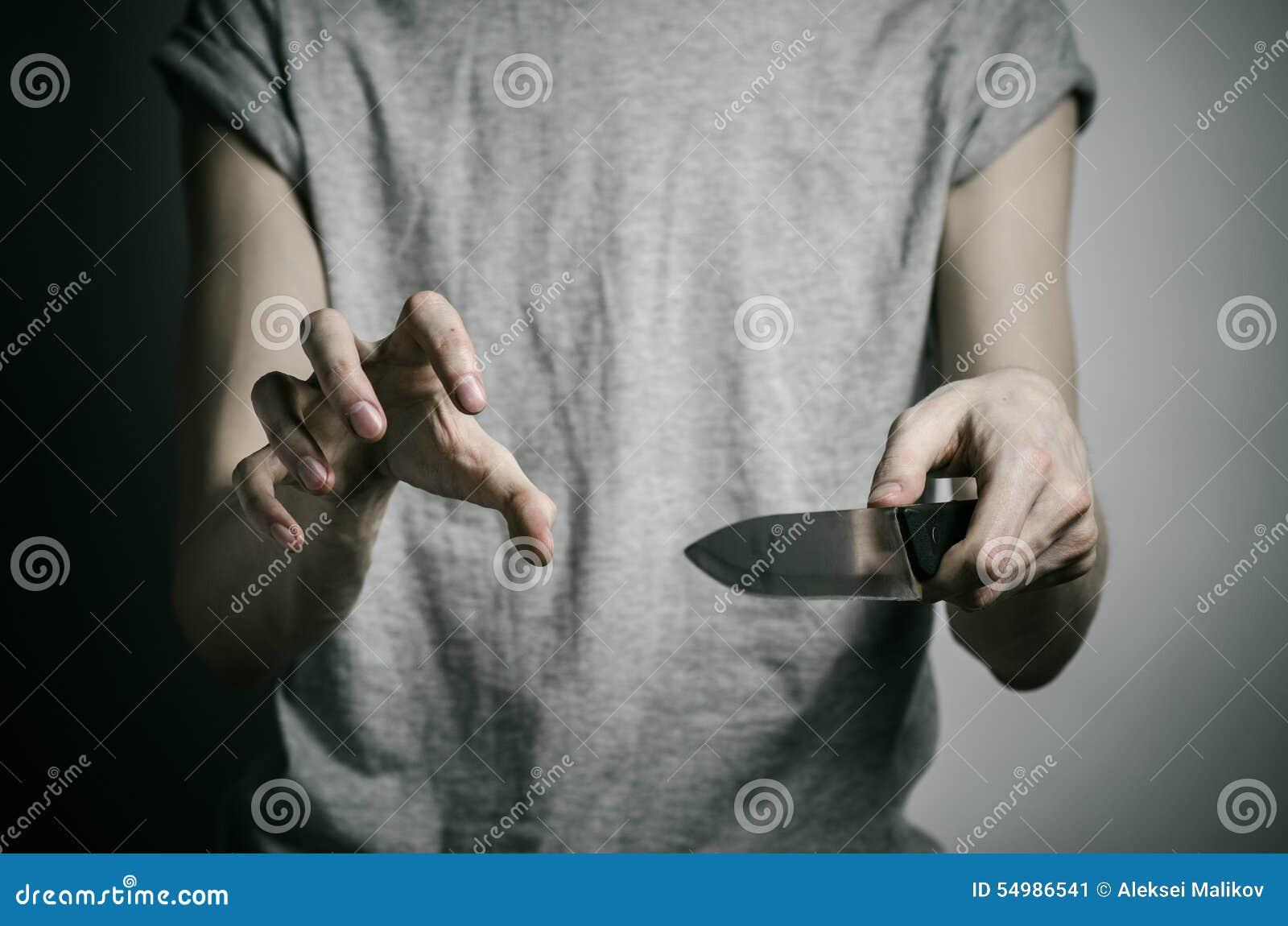 Mord- und Halloween-Thema: ein Mann, der ein Messer auf einem grauen Hintergrund hält