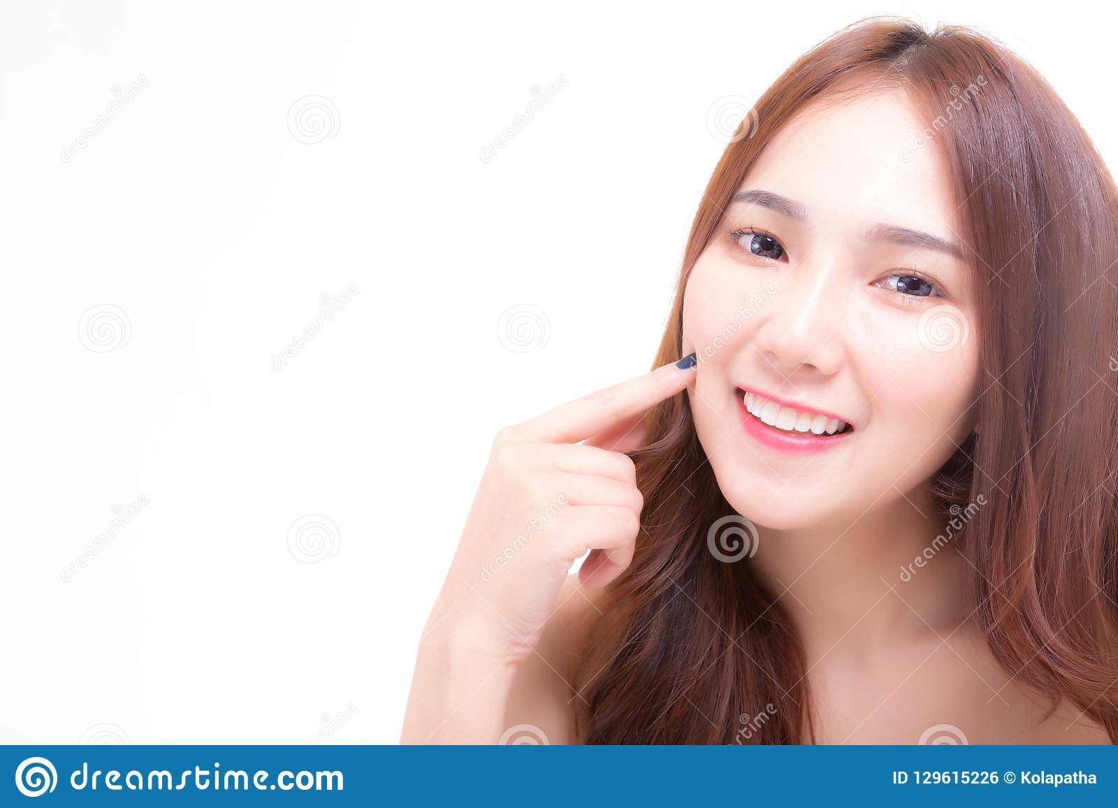 Mordente bonito de encantamento da imprensa do dedo do uso da jovem mulher, mostrando a pele da cara lisa e macia com sorriso
