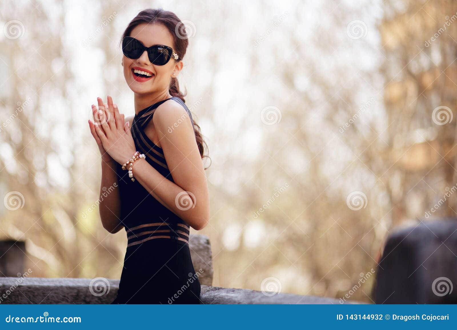 Morena adorável, elegante no vestido preto  sexy , óculos de sol, rabo de cavalo do cabelo e estada bonita da cara no balcão