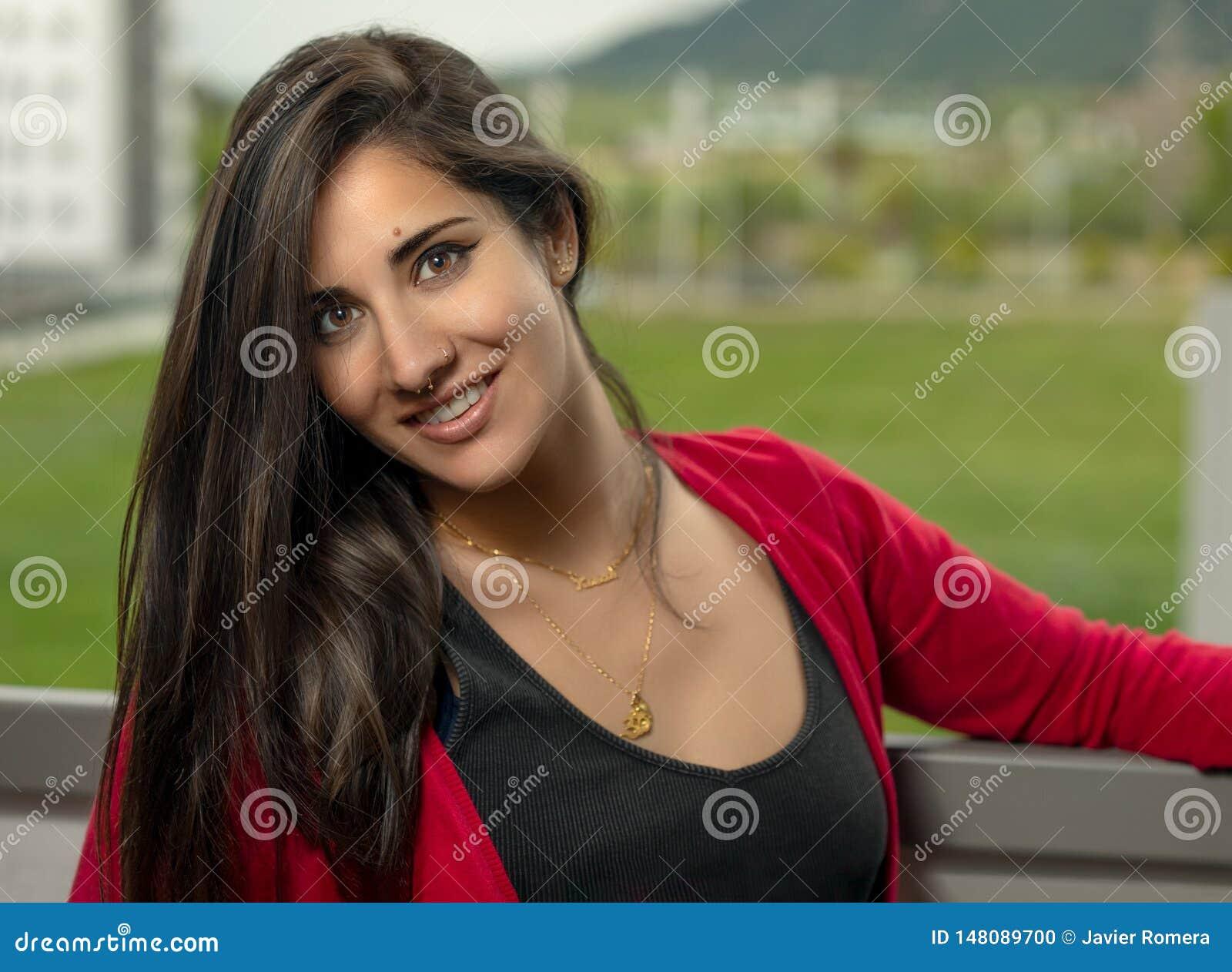 Morena bonita e menina longa do cabelo com um casaco de lã vermelho que sorriem na câmera