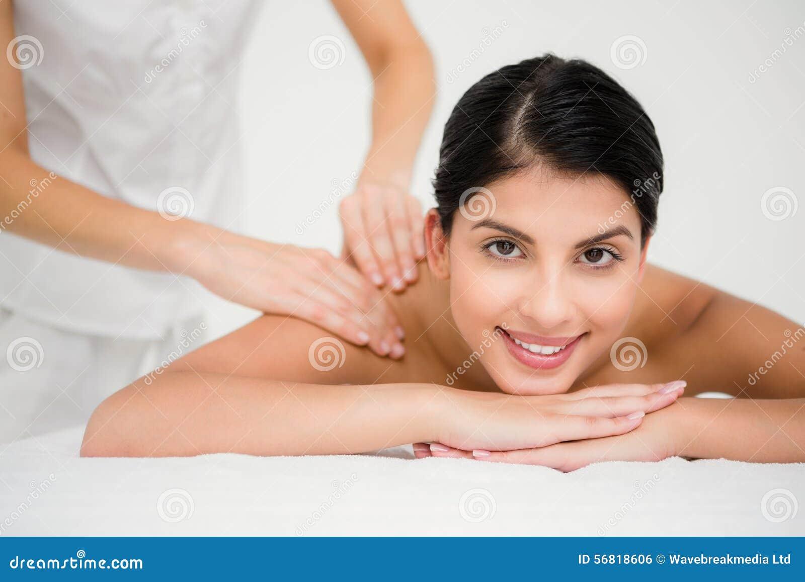 Morena bonita que aprecia uma massagem que sorri na câmera