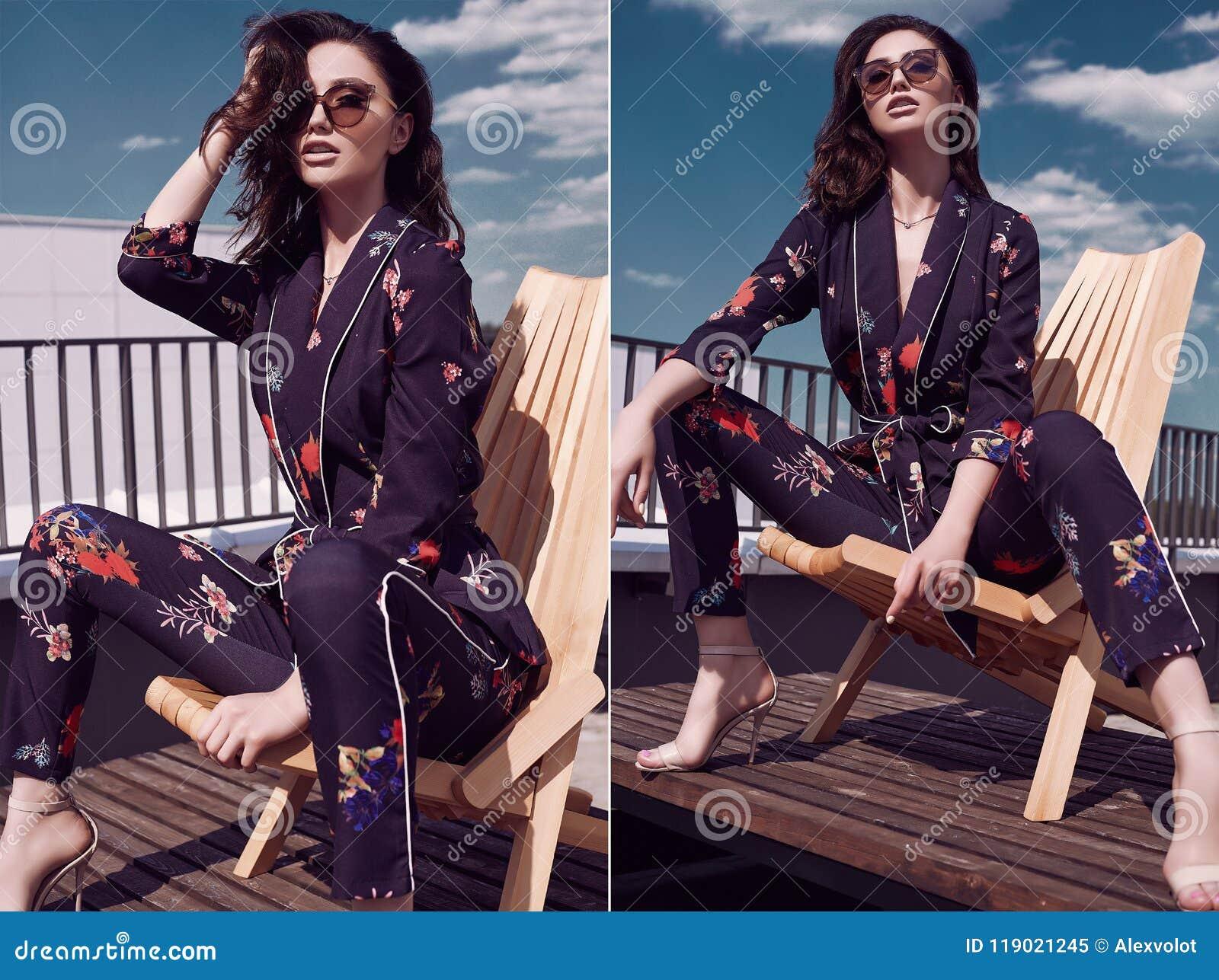 Morena brilhante lindo no vestido vívido que senta-se em uma cadeira de madeira
