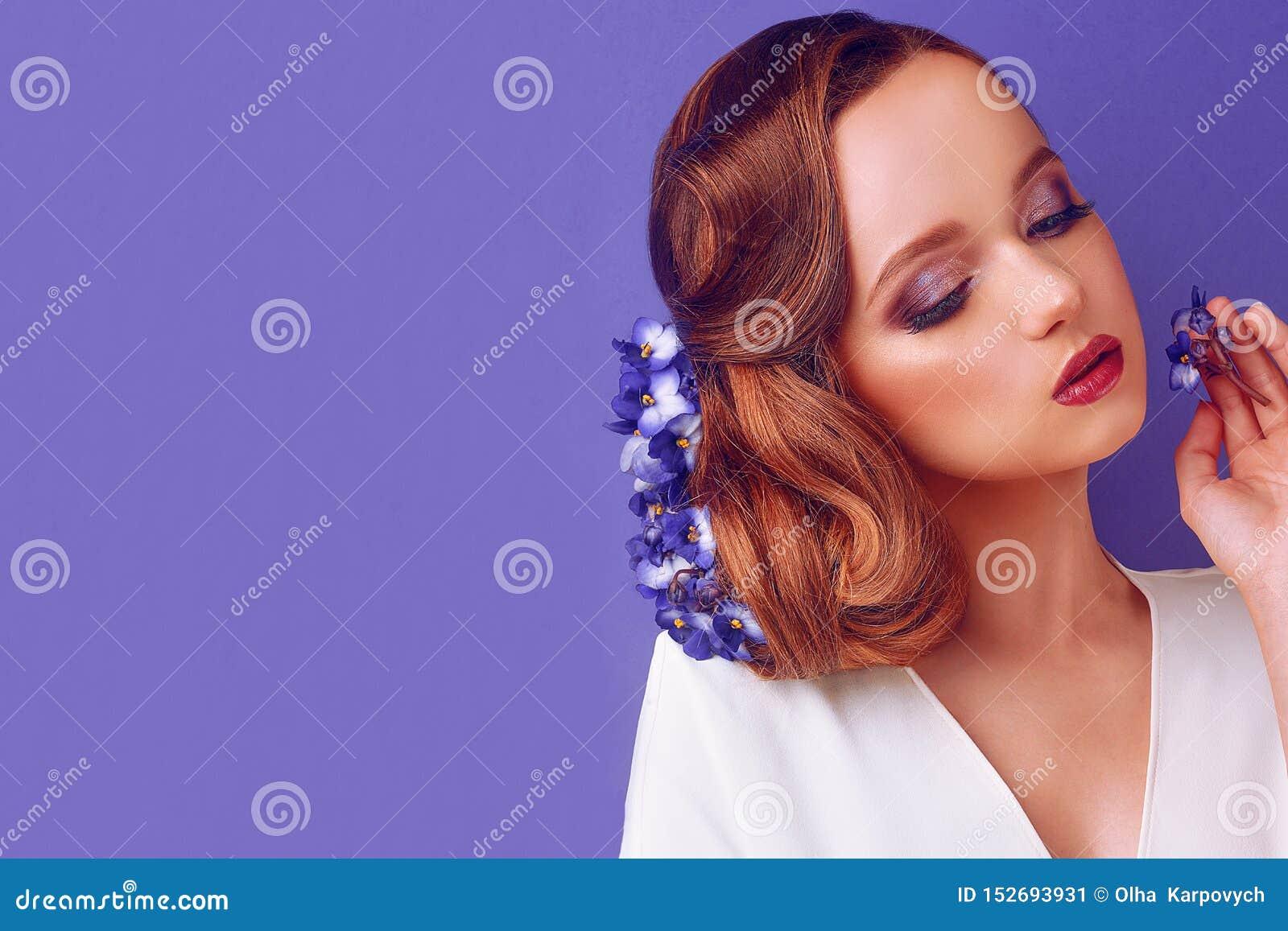 Morena em um fundo azul Menina com composição e penteado profissionais Sal?o de beleza de beleza Menina com as flores azuis em se