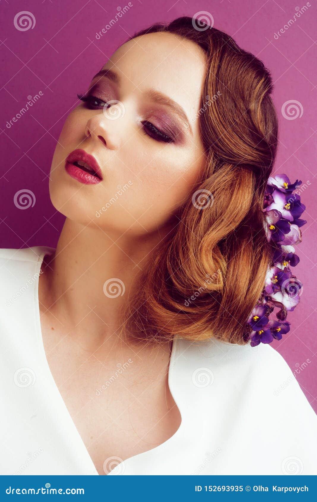 Morena em um fundo cor-de-rosa Menina com composição e penteado profissionais Cabelo que denomina, salão de beleza do vapor Bar d