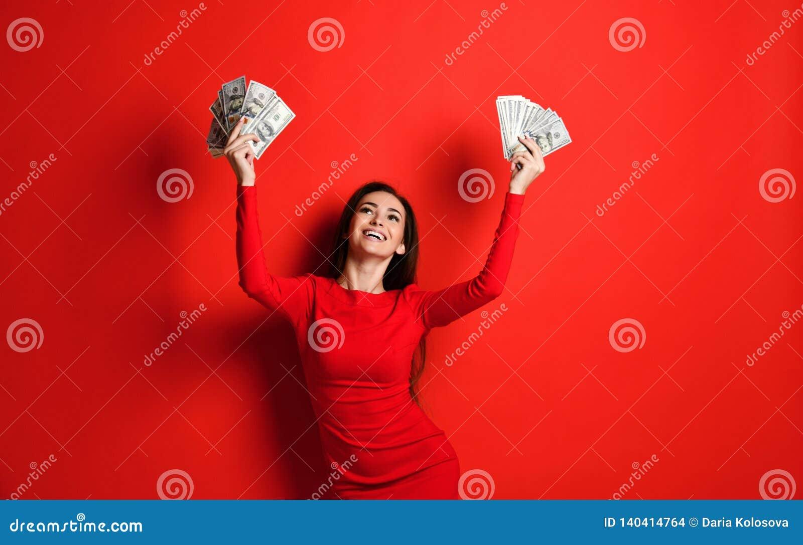 A morena insolente nova em um vestido vermelho exulta em uma grande quantidade de dinheiro em suas mãos que ganha