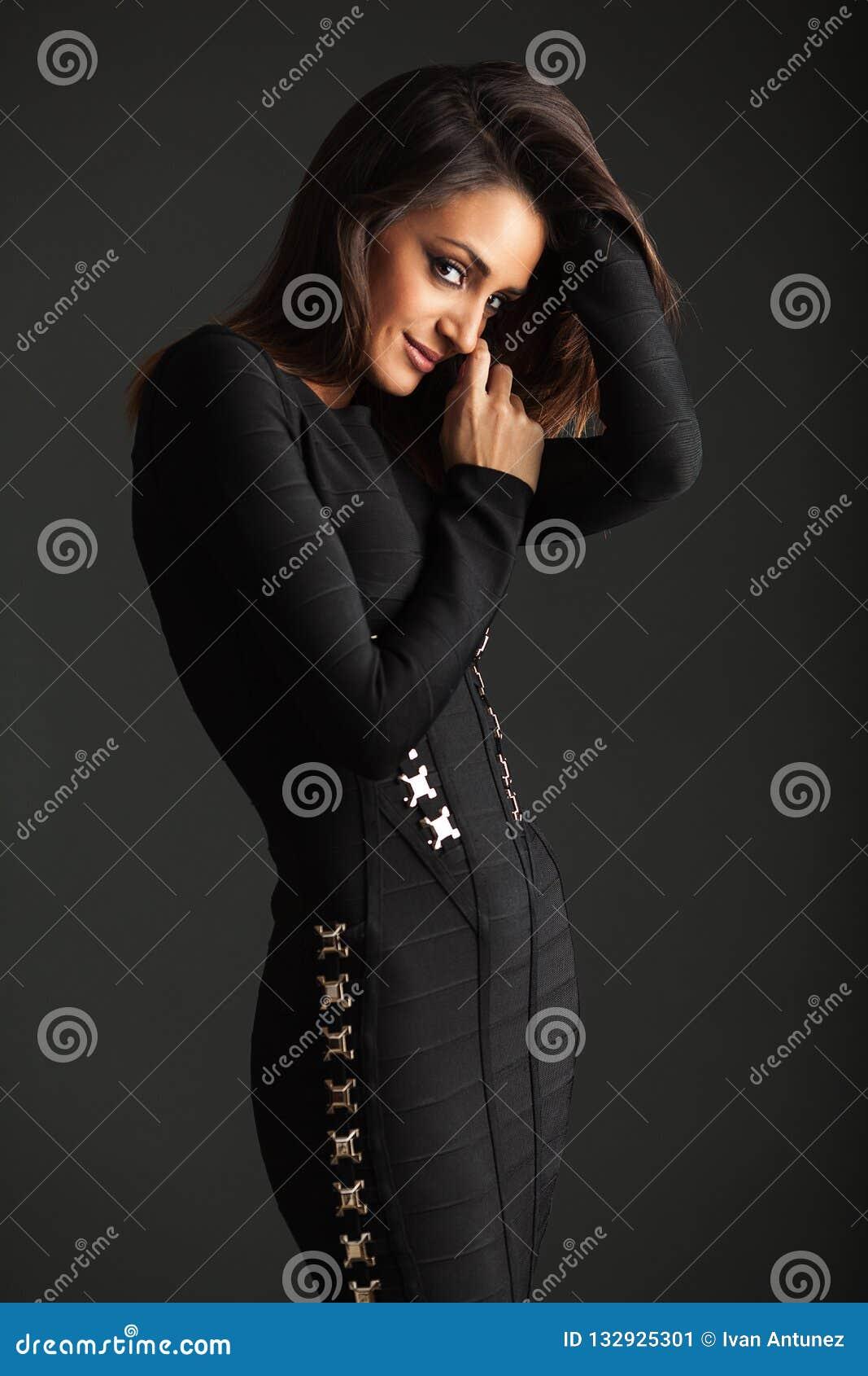 Morena no vestido preto que levanta no estúdio