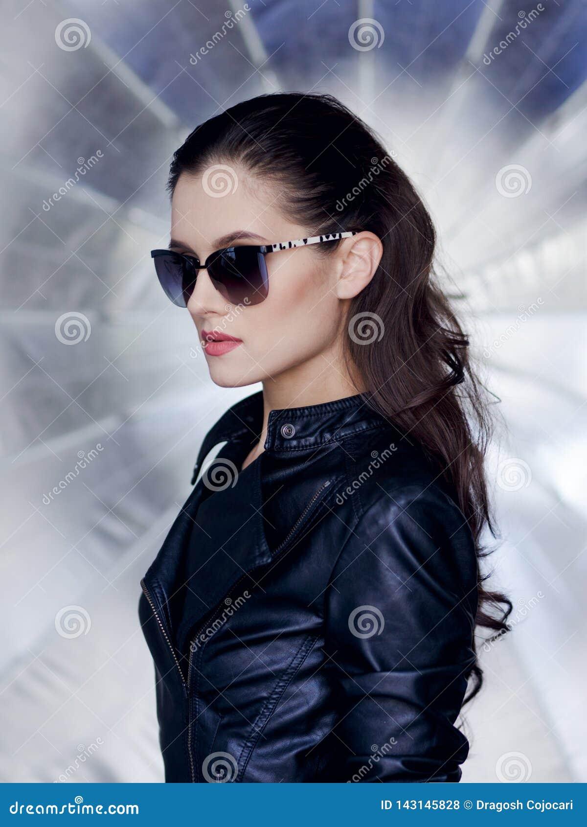 Morena segura e  sexy  com cara bonita, os óculos de sol à moda, o casaco de cabedal preto e penteado rebelde