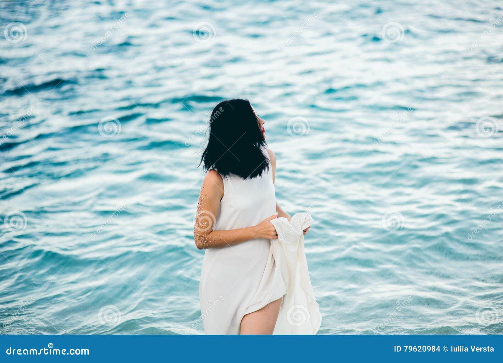 Morena  sexy  nova na água azul em um vestido branco na praia