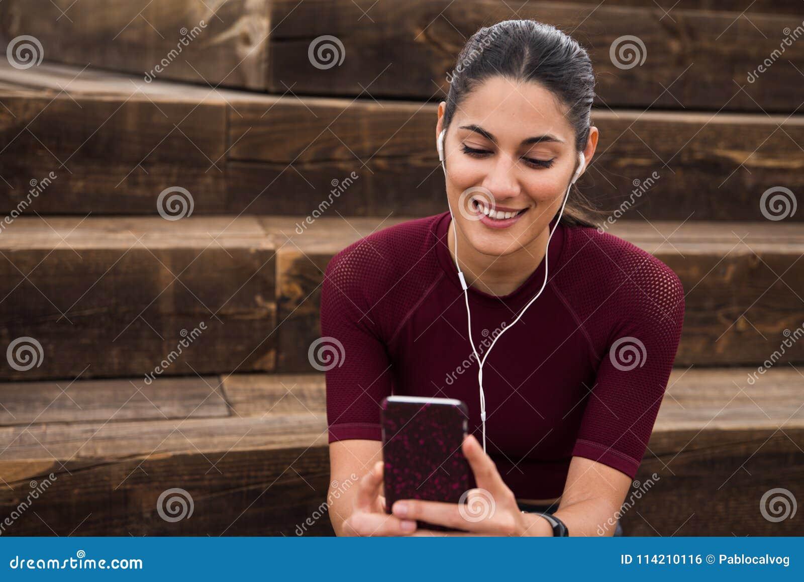 Morenita bonita sonriente que se sienta en las escaleras