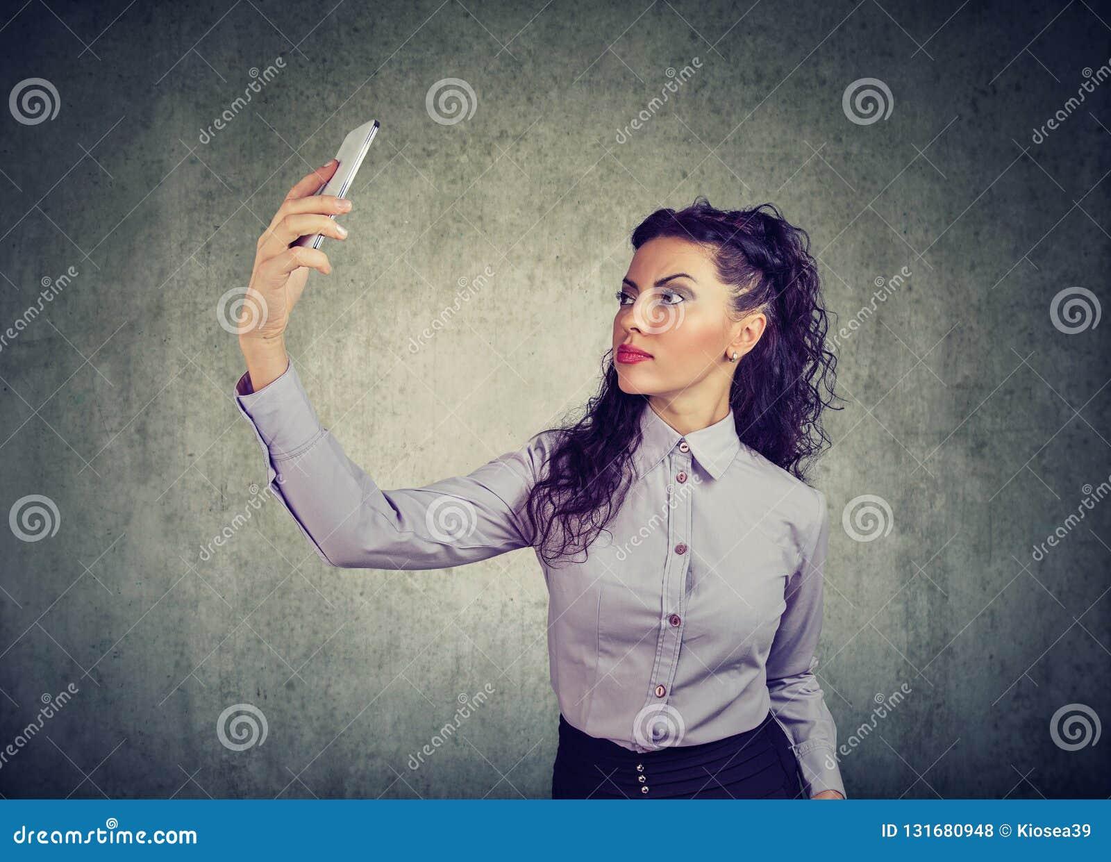 Morenita hermosa en equipo formal usando selfie del smartphone y el tomar en fondo gris