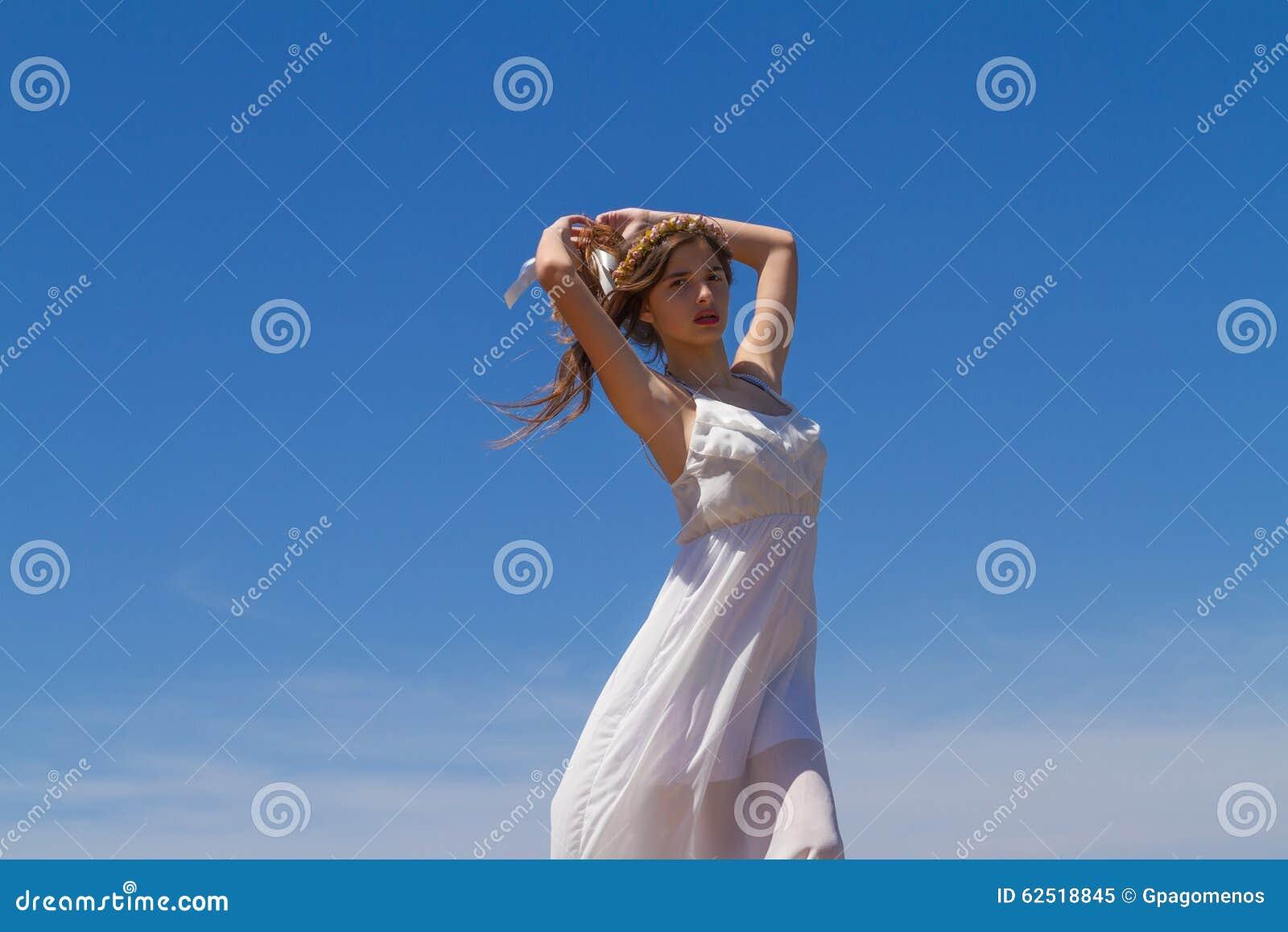 Morenita joven en el vestido débil blanco