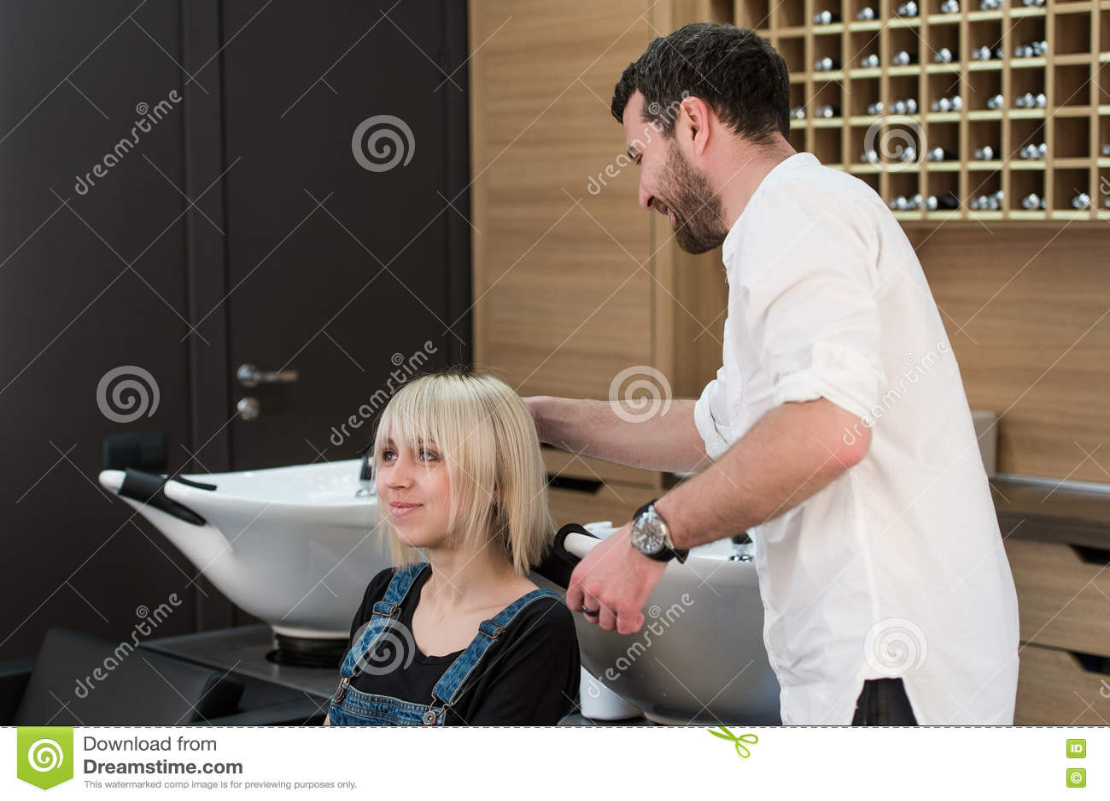 Moreno alegre que faz o penteado para a menina loura adolescente no bar do cabeleireiro