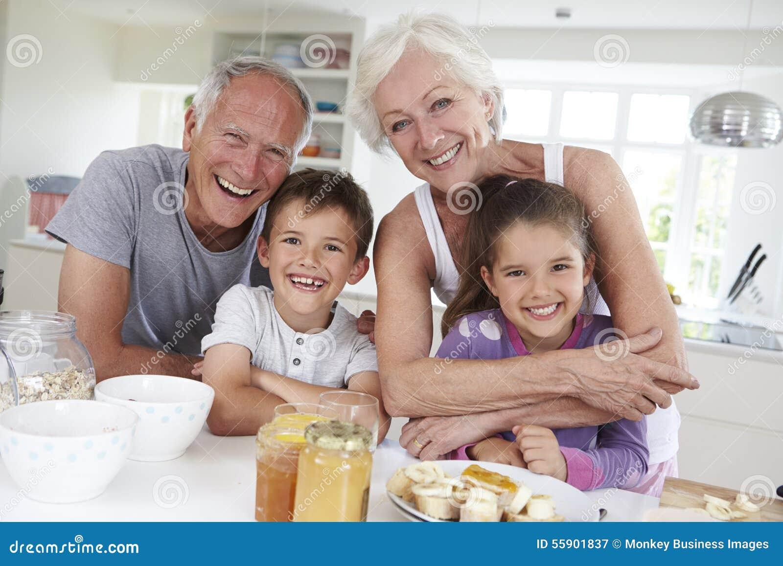 Morföräldrar med barnbarn som äter frukosten i kök