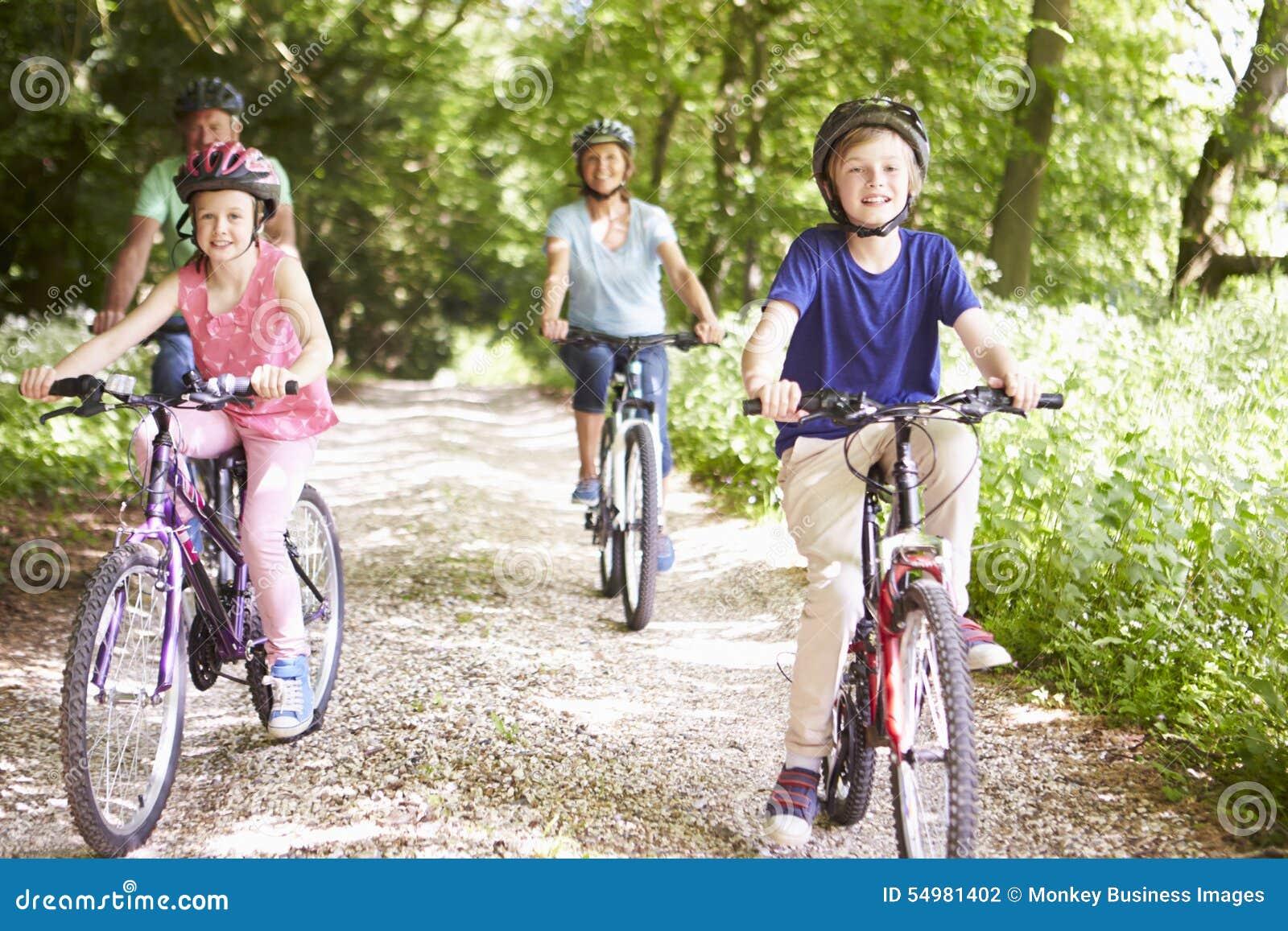 Morföräldrar med barnbarn som cyklar i bygd