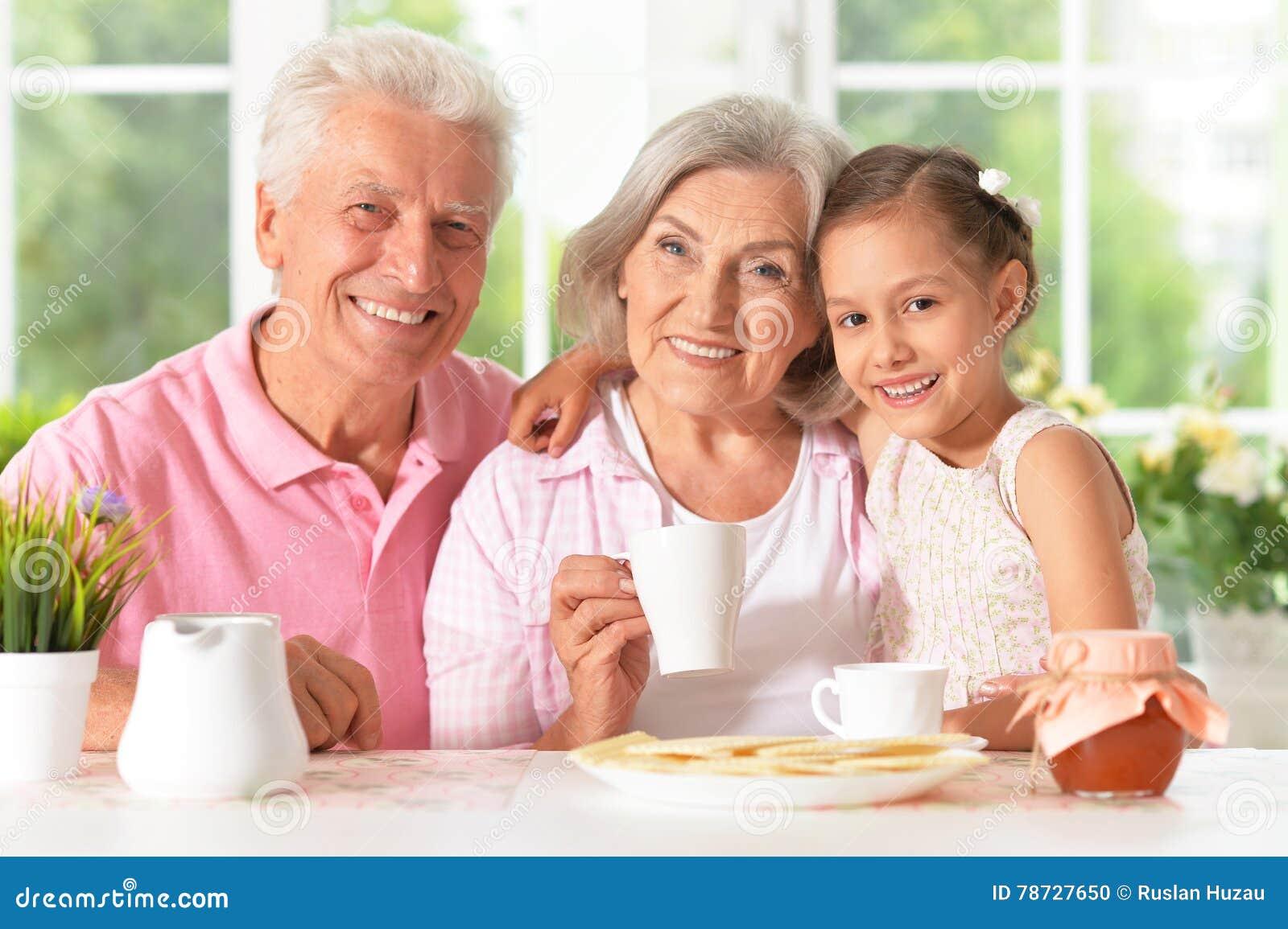 Morföräldrar med sondottern som dricker te