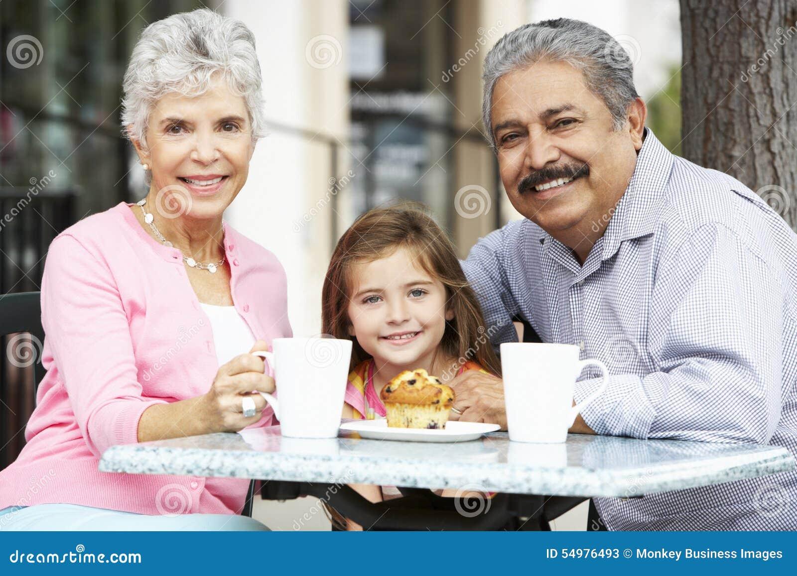 Morföräldrar med sondottern som tycker om mellanmålet på utomhus- CafÅ ½