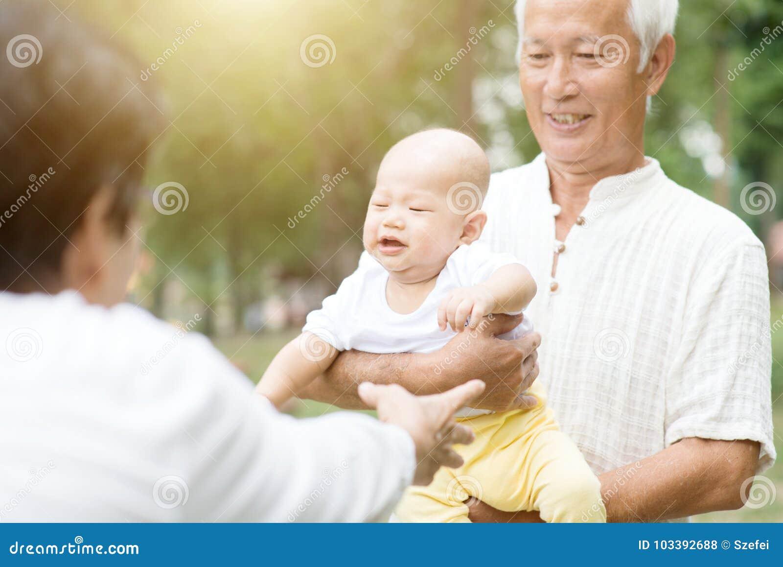 Morföräldrar och barnbarn som har roligt utomhus