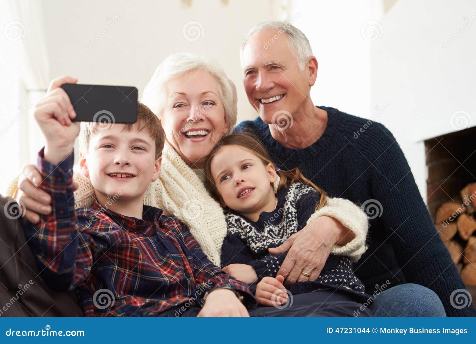 Morföräldrar och barnbarn som sitter på Sofa Taking Selfie