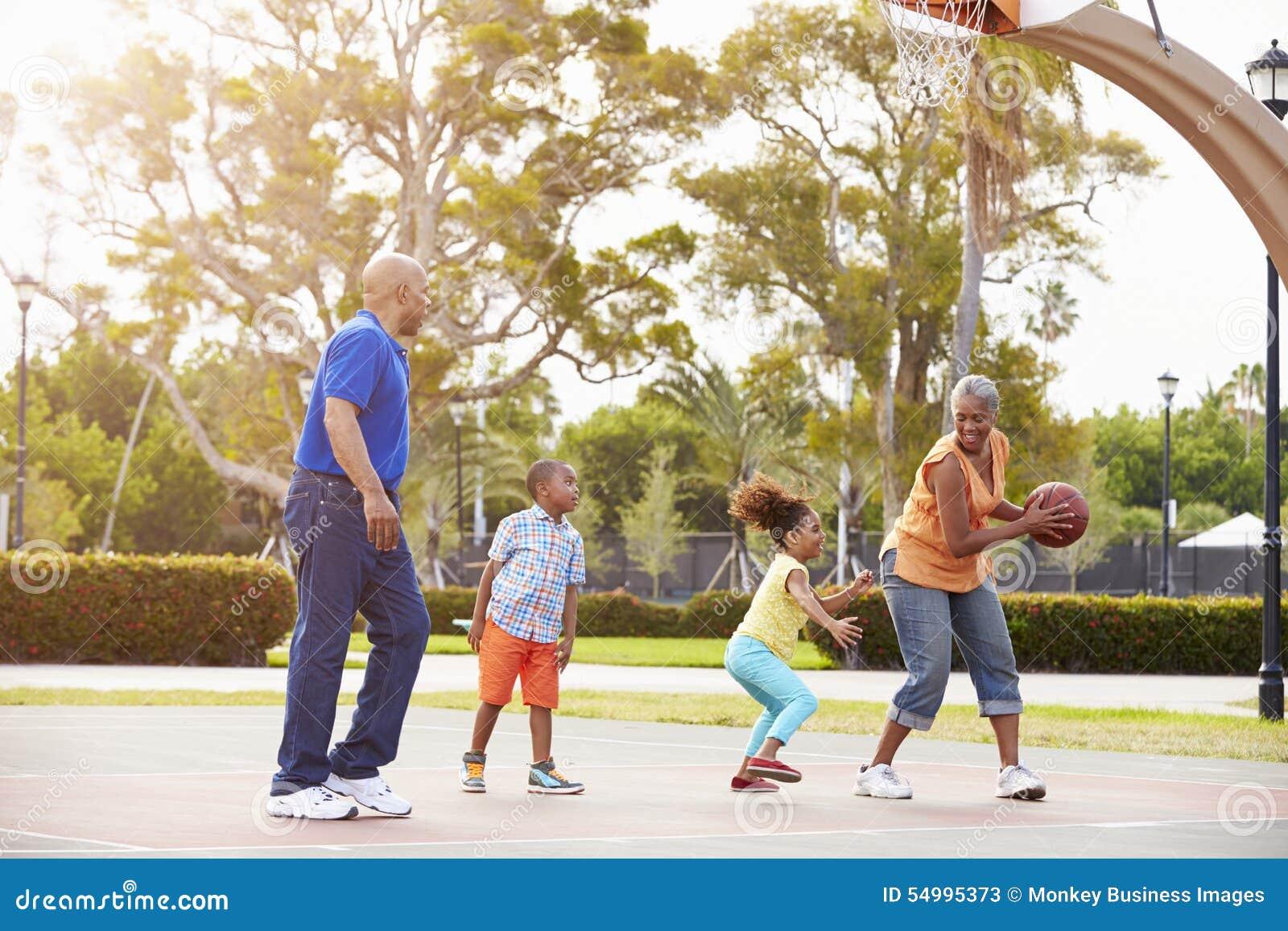 Morföräldrar och barnbarn som spelar basket tillsammans
