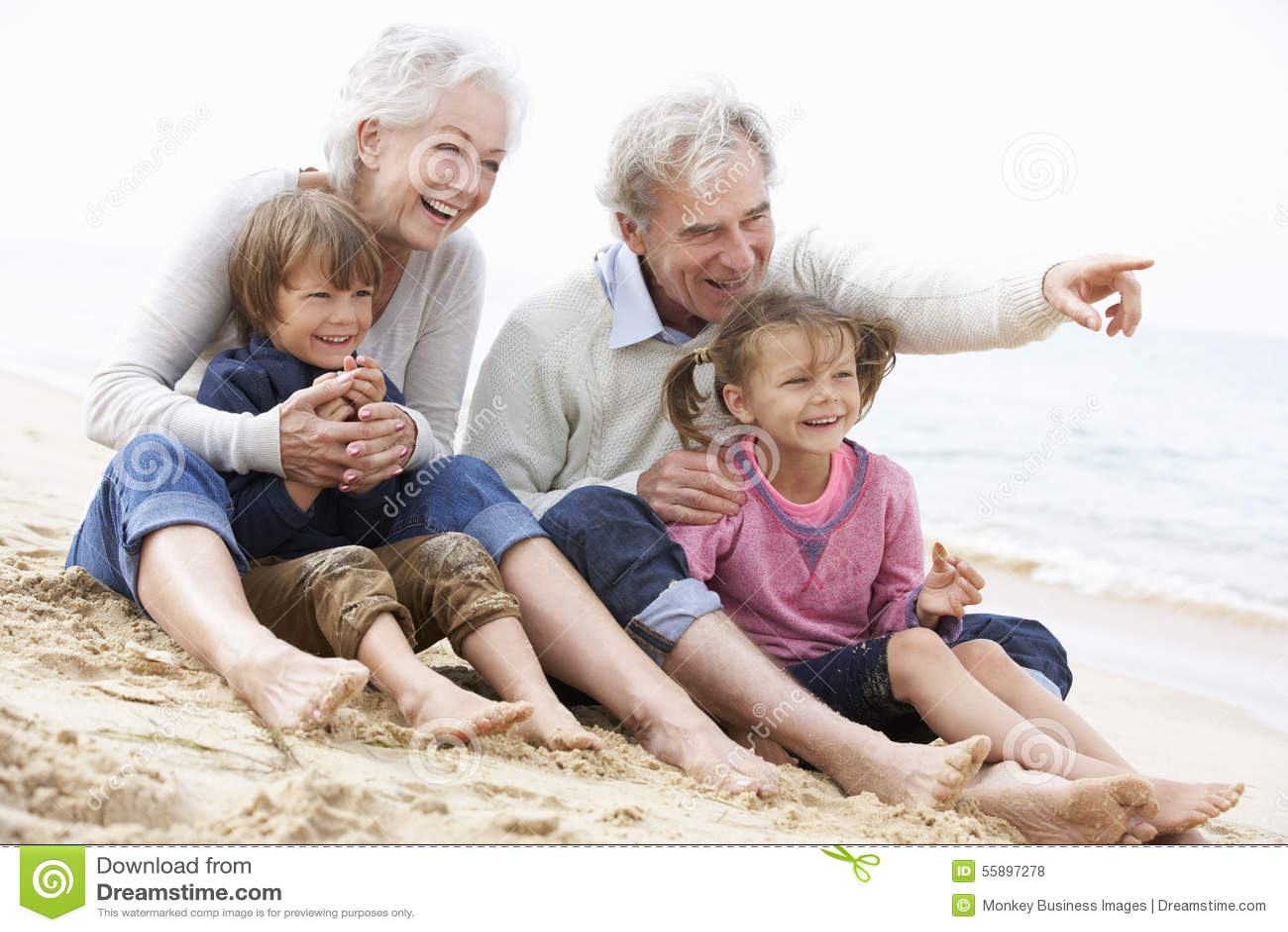 Morföräldrar och barnbarn som tillsammans sitter på stranden
