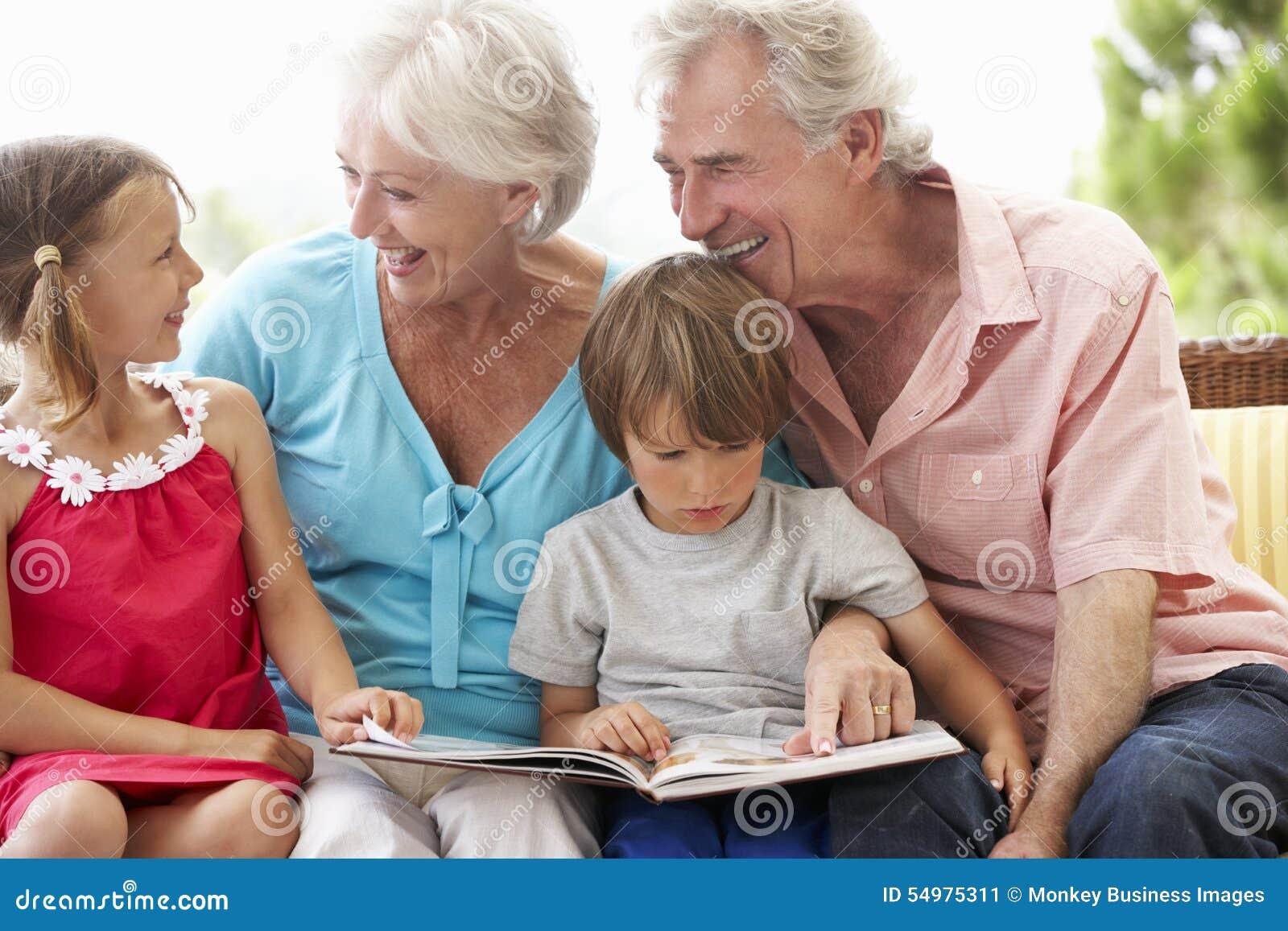 Morföräldrar och barnbarnläsebok på trädgårds- Seat