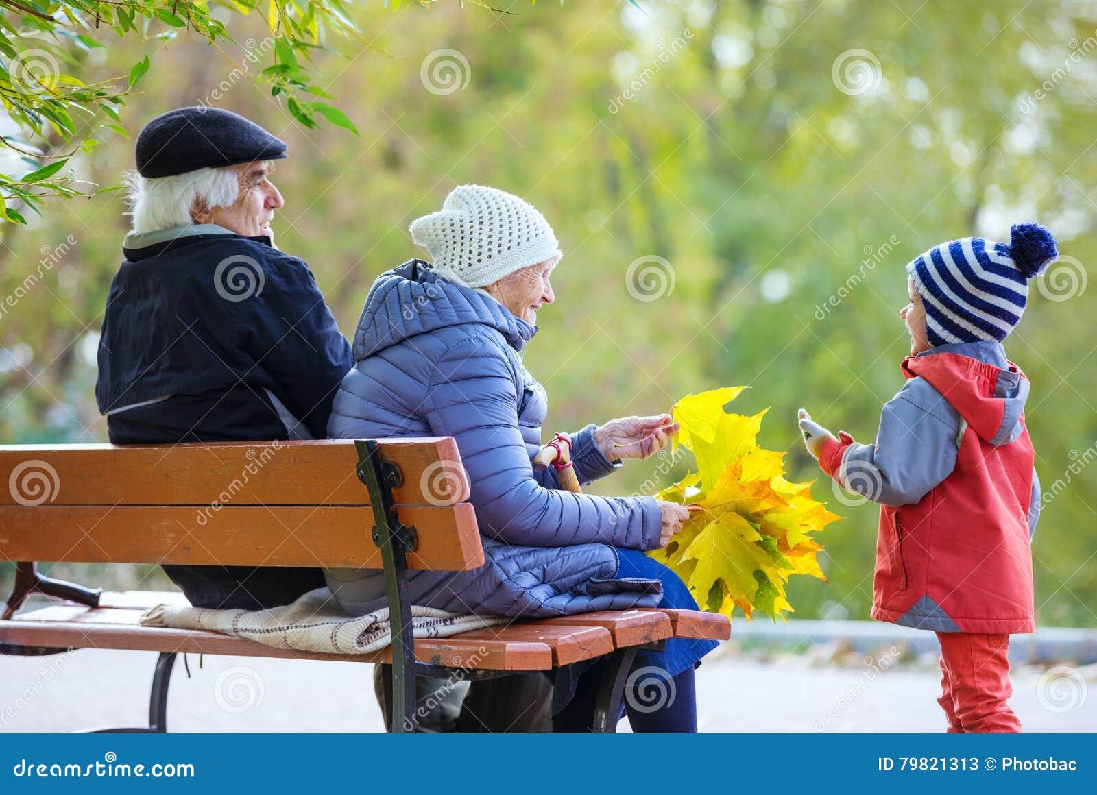 Morföräldrar och sonson som tycker om härlig höstdag
