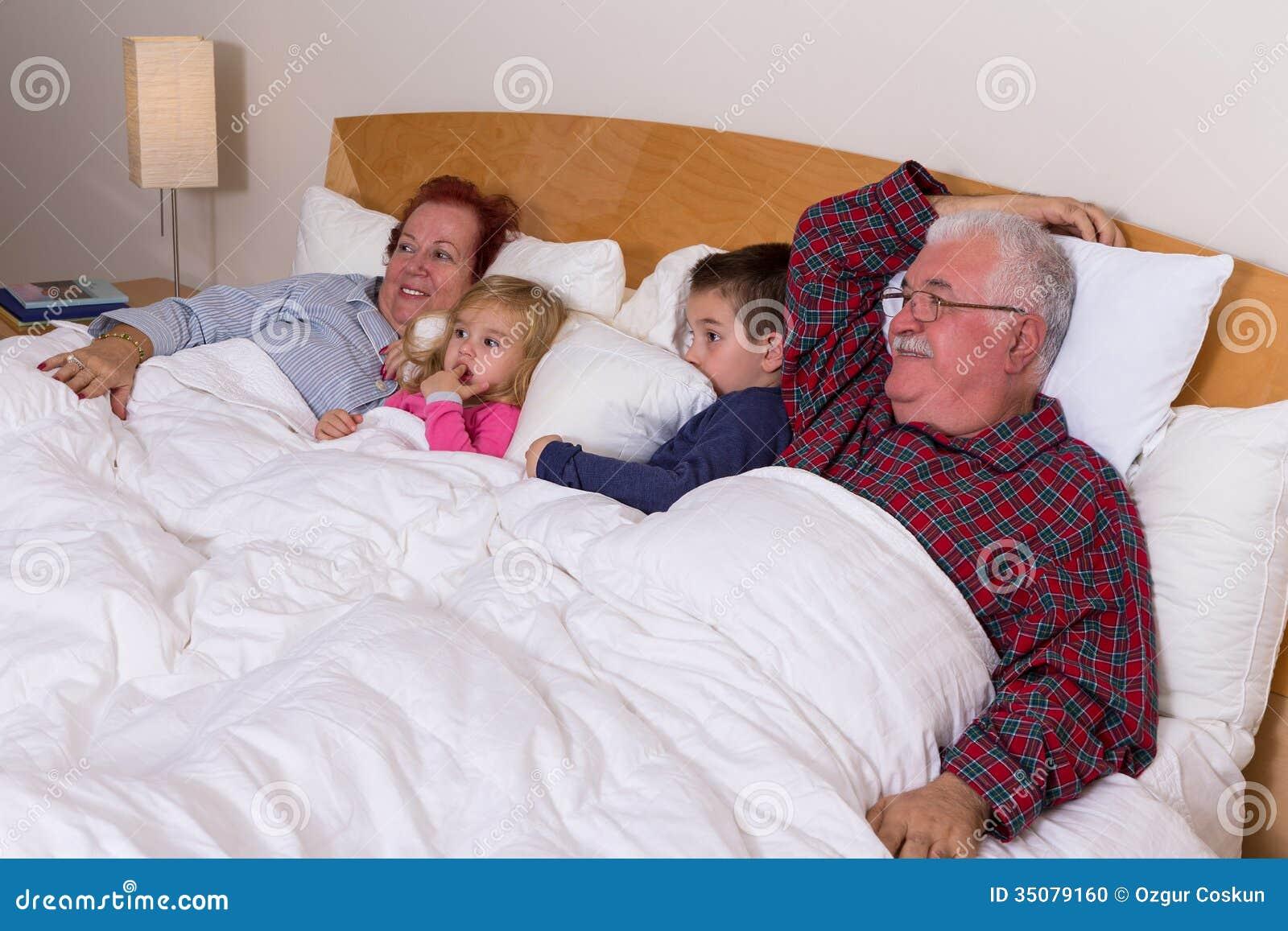 Morföräldrar som håller ögonen på TV i sängen med deras storslagna ungar